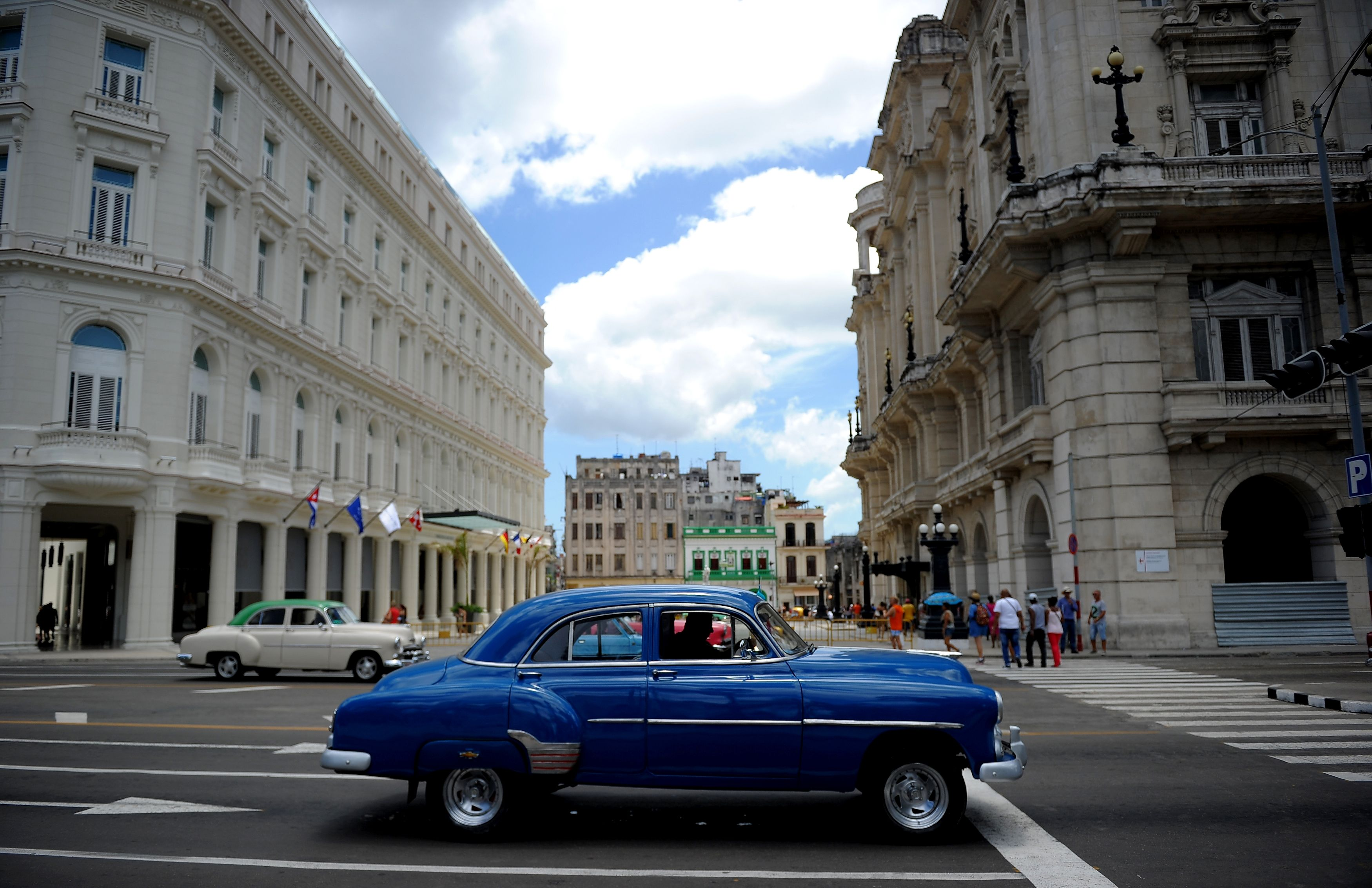 An American vintage car drives near the Manzana Kempinski Hotel, the first luxury tourist facility in Cuba, on May 22, 2017.