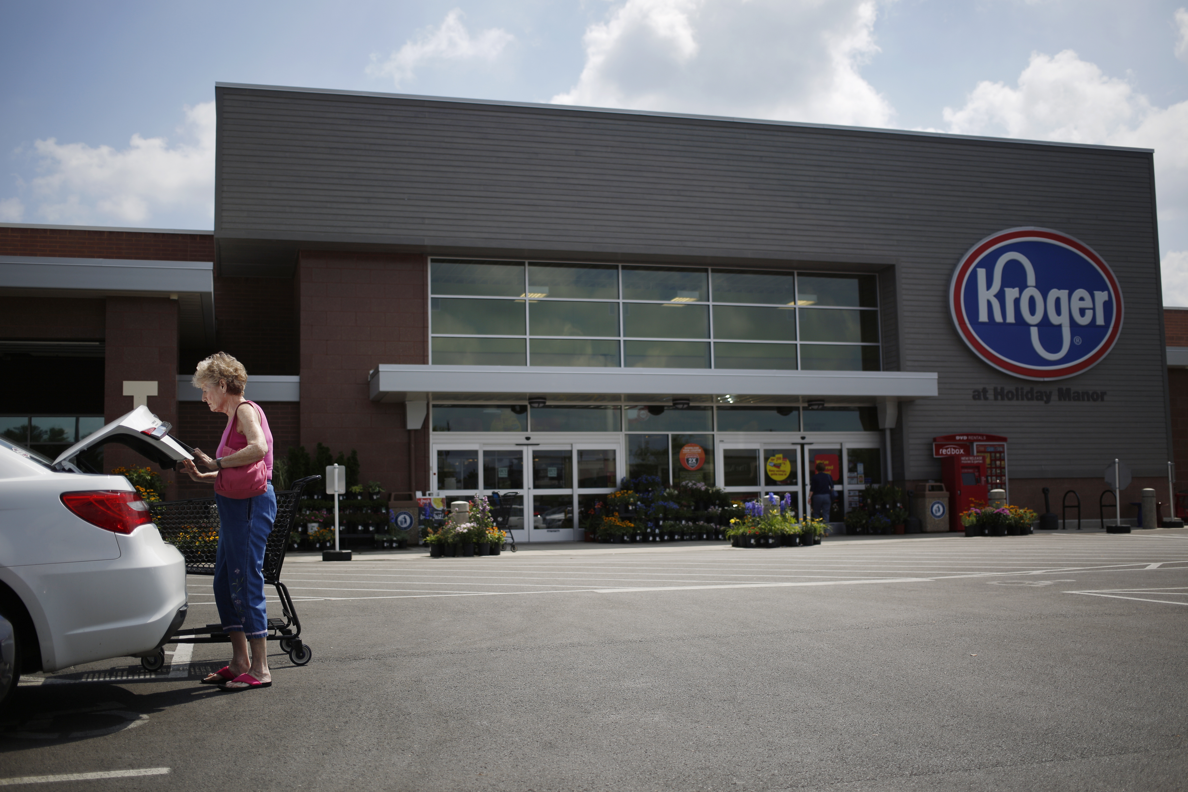 A customer loads groceries into a car outside a Kroger Co. grocery store in Louisville, Kentucky, U.S., on Wednesday, June 14, 2017.