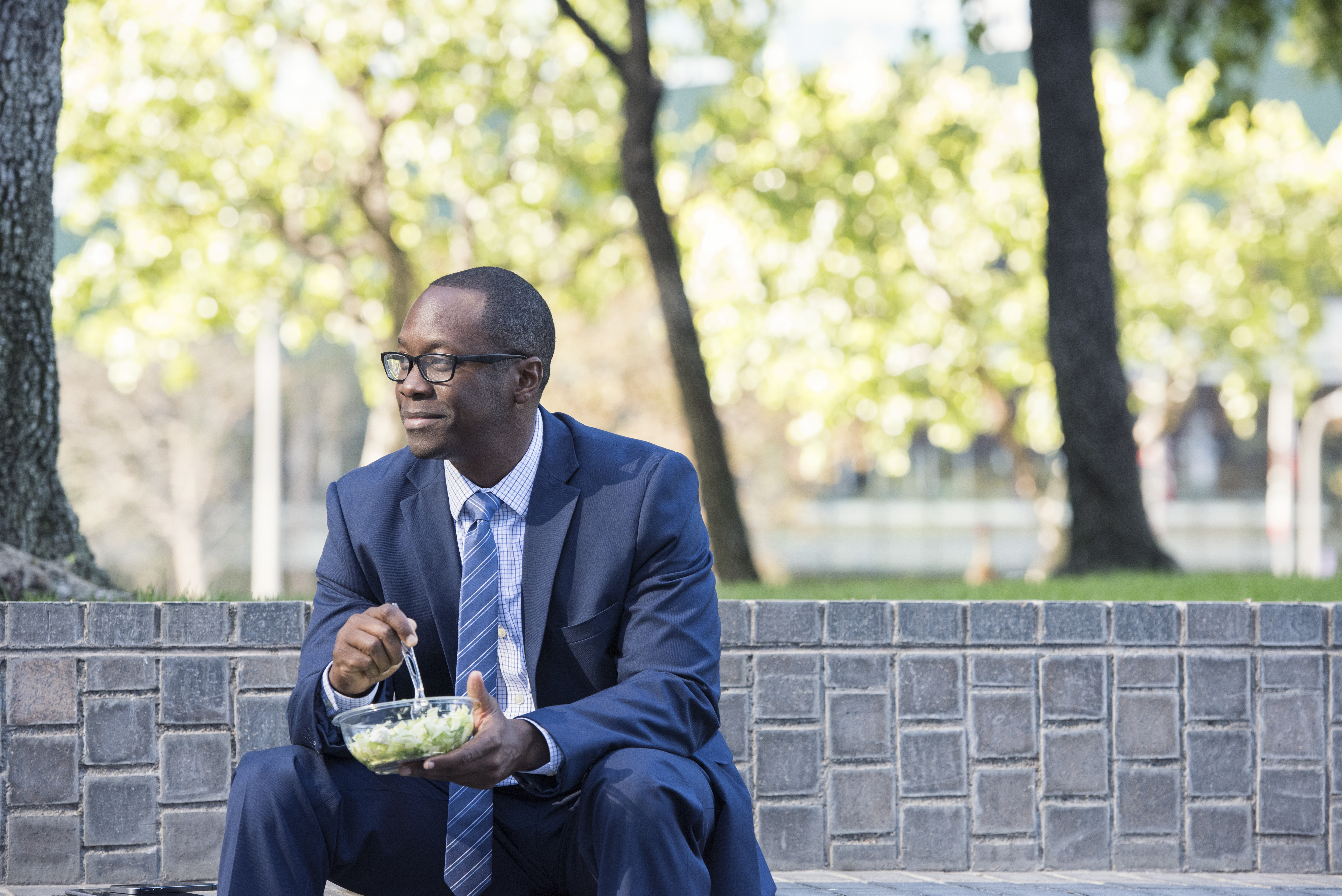 Businessman sitting on outdoor stairs having lunch