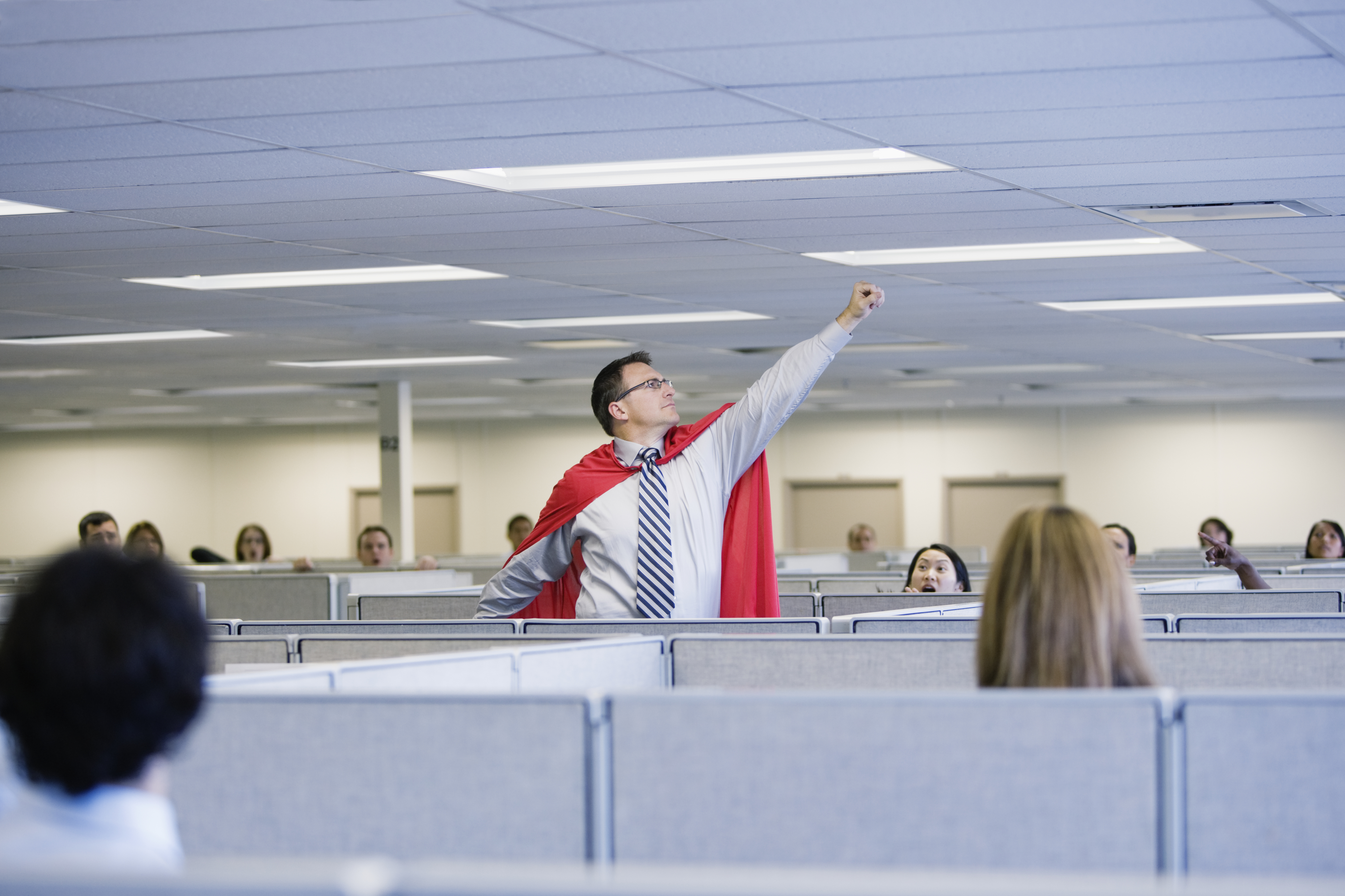 Man wearing superhero costume in office pretending to fly