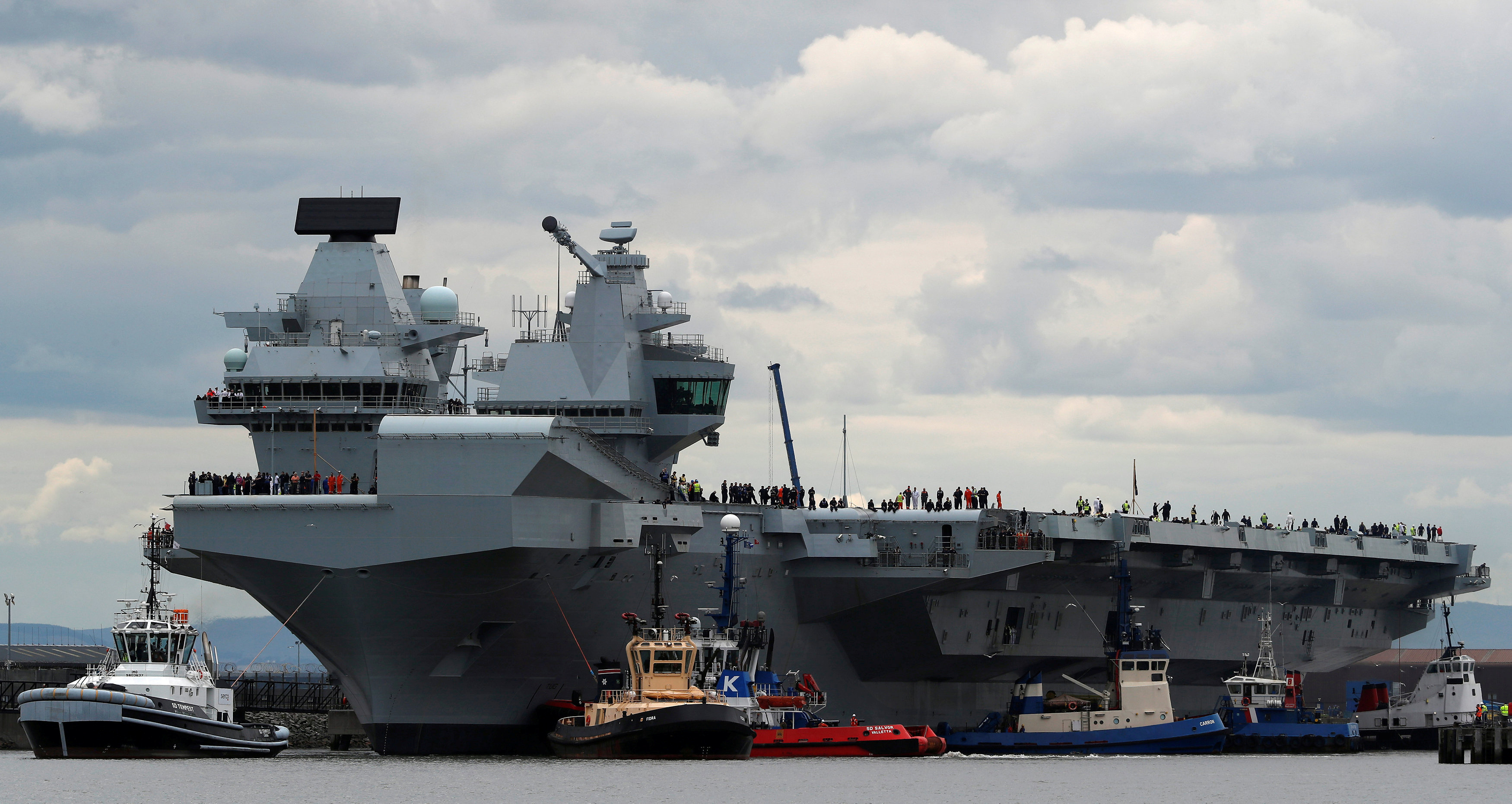 The British aircraft carrier HMS Queen Elizabeth is pulled from its berth by tugs before its maiden voyage, in Rosyth, Scotland