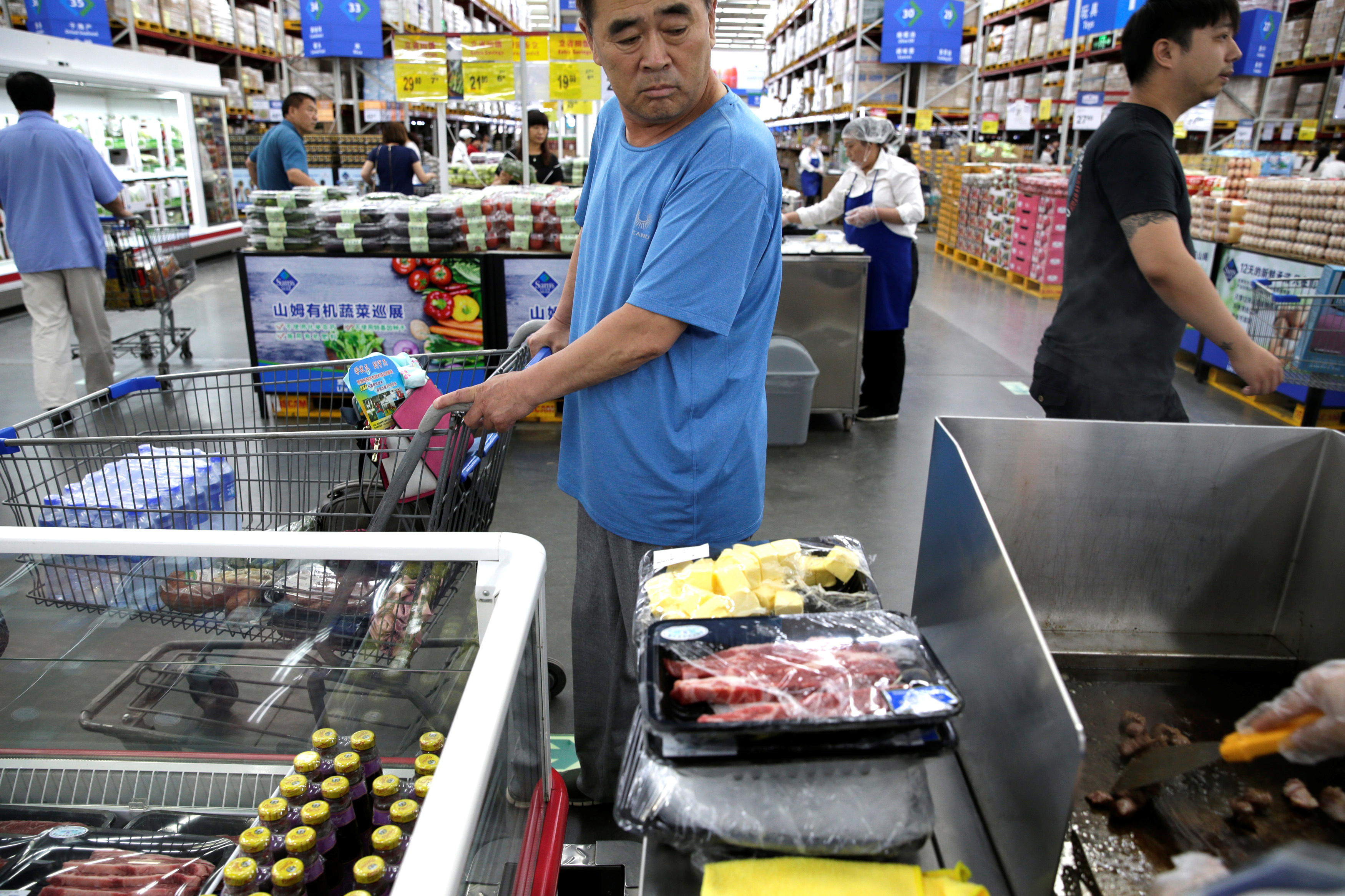 A customer looks at the beef steaks for sale at a Sam's Club store of Wal-Mart in Beijing