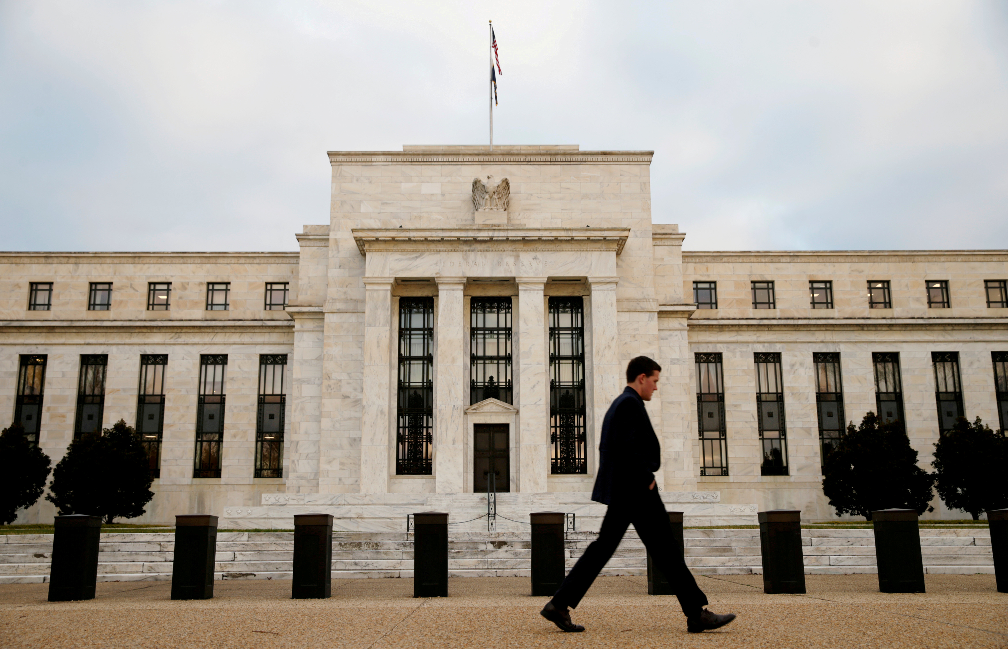 FILE PHOTO: A man walks past the Federal Reserve Bank in Washington DC