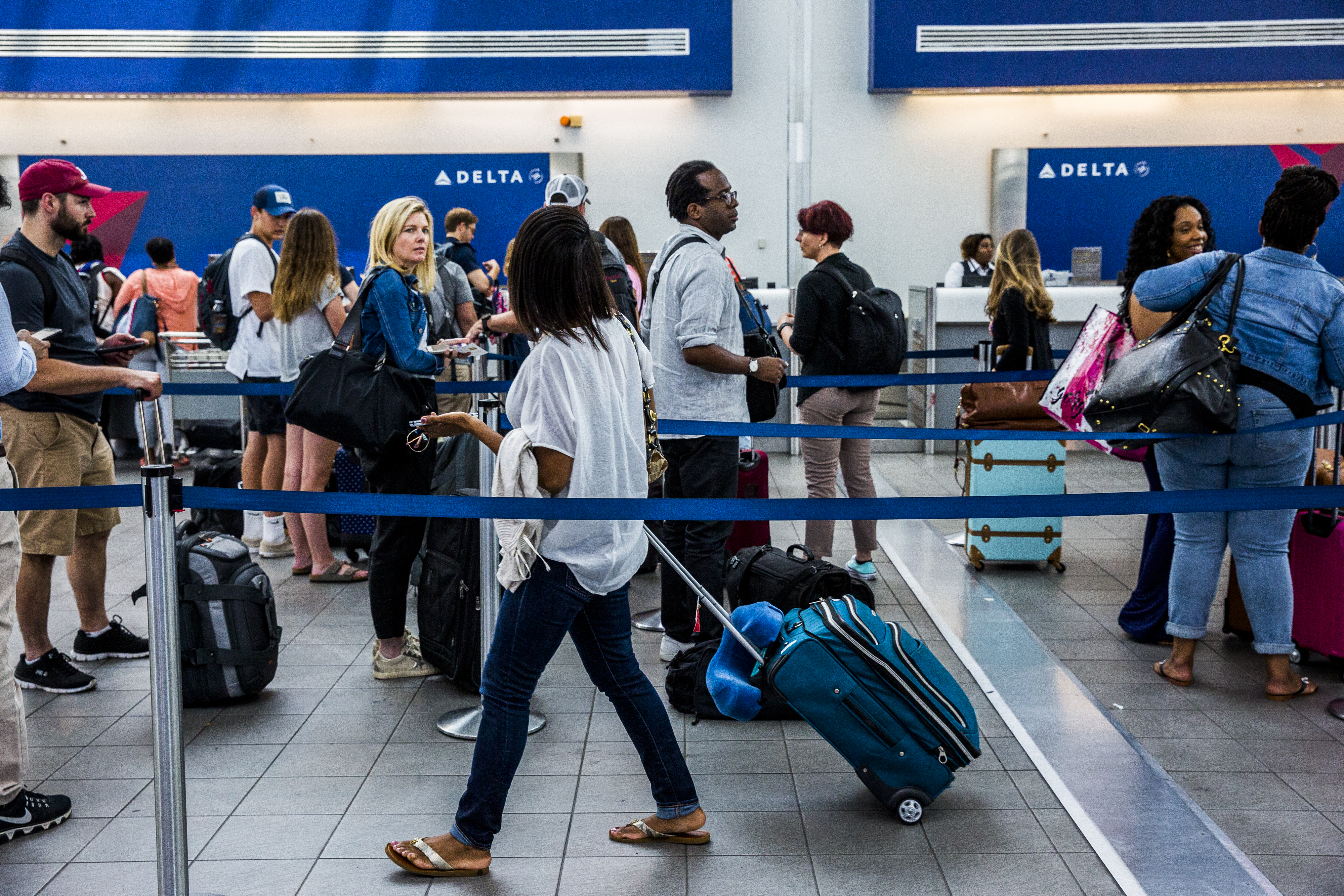Travelers wait in line at the Delta Air Lines ticket counter inside LaGuardia Airport (LGA) in New York, U.S., on Thursday, June 29, 2017.