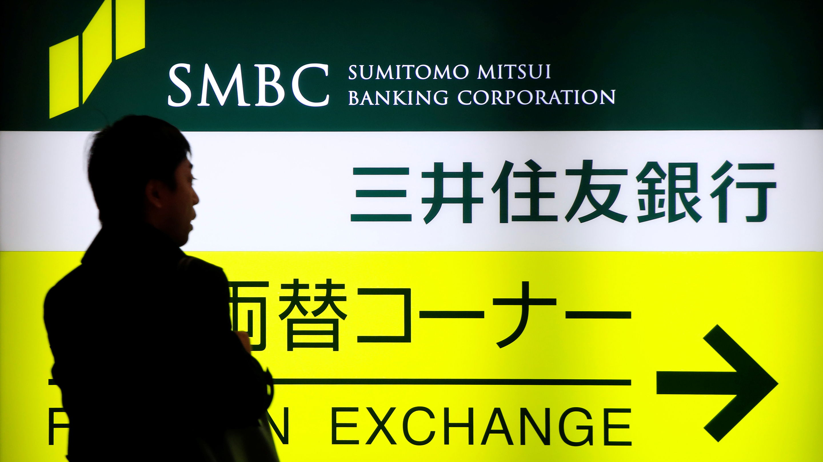 A man walks past a sign board of Sumitomo Mitsui Banking Corporation, part of SMFG outside its branch in Tokyo