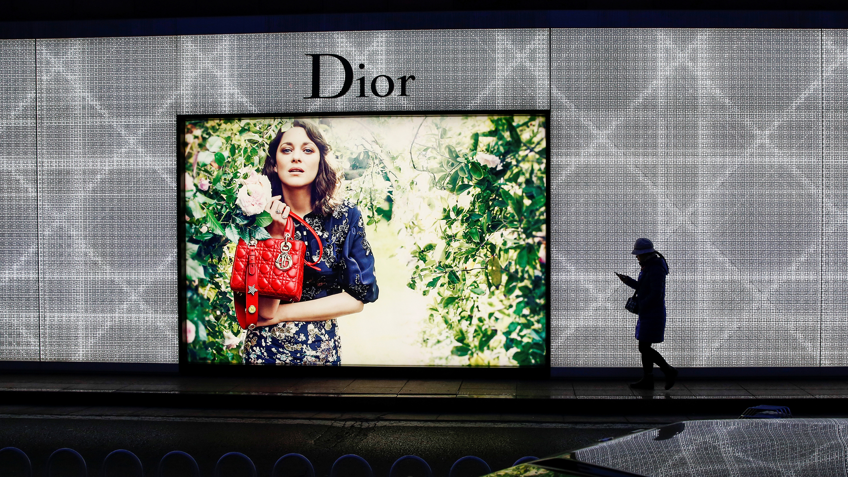 A woman walks past an advertising display of the Dior luxury goods company outside a department store in Beijing
