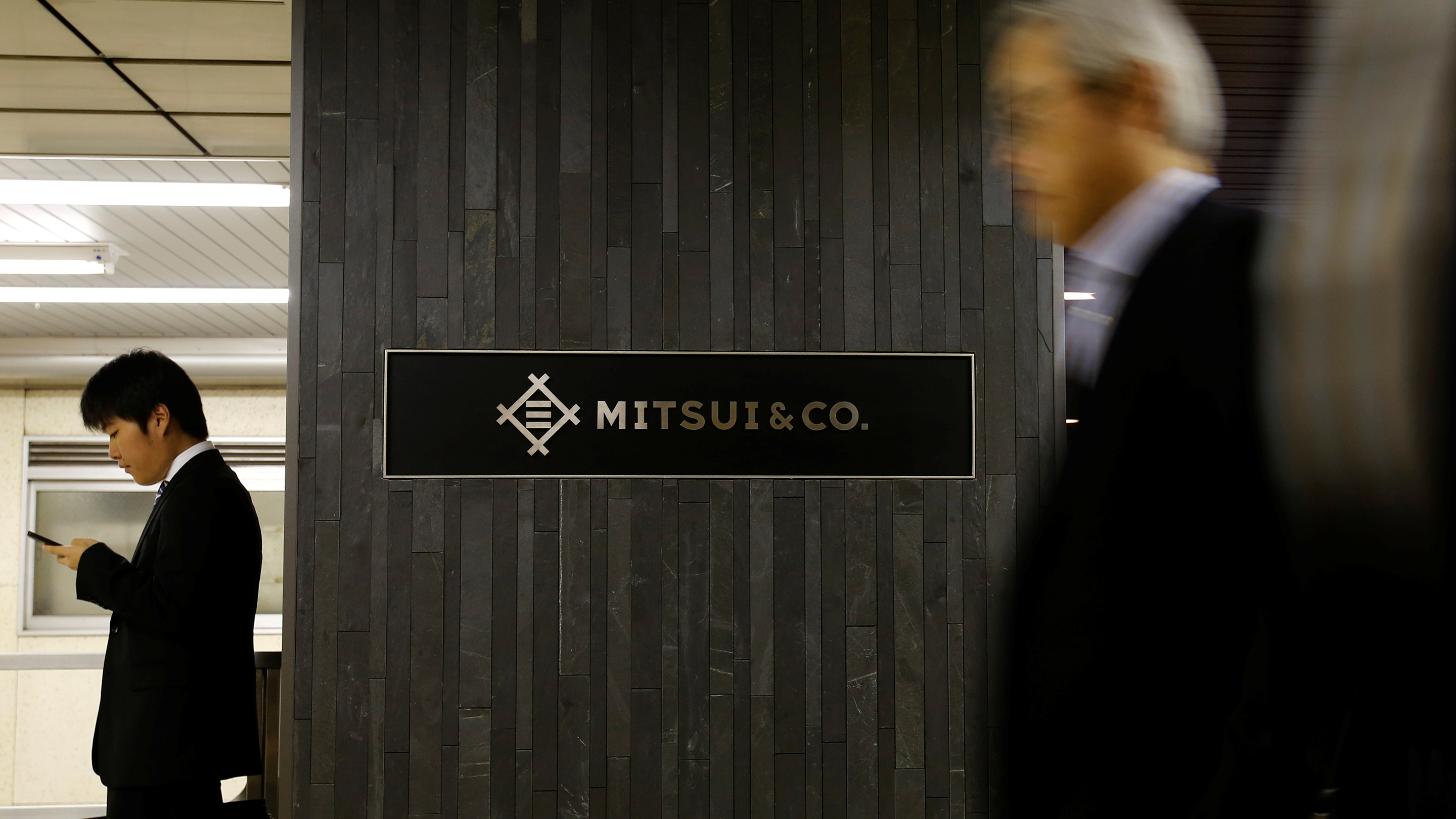 Men walk past the logo of Japanese trading company Mitsui & Co. in Tokyo