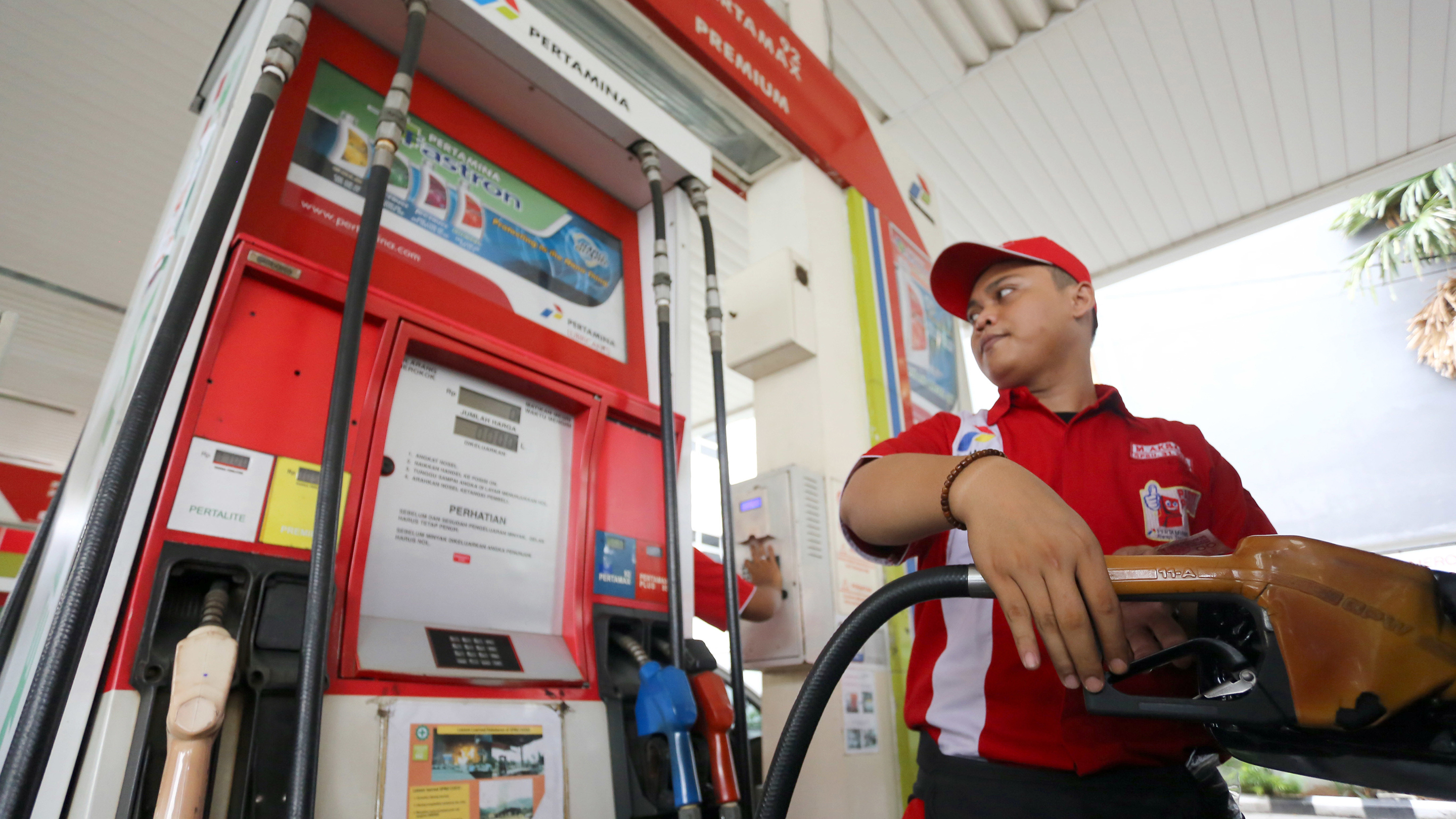 A gasoline boy fuels up a vehicle. Towards the Indonesian