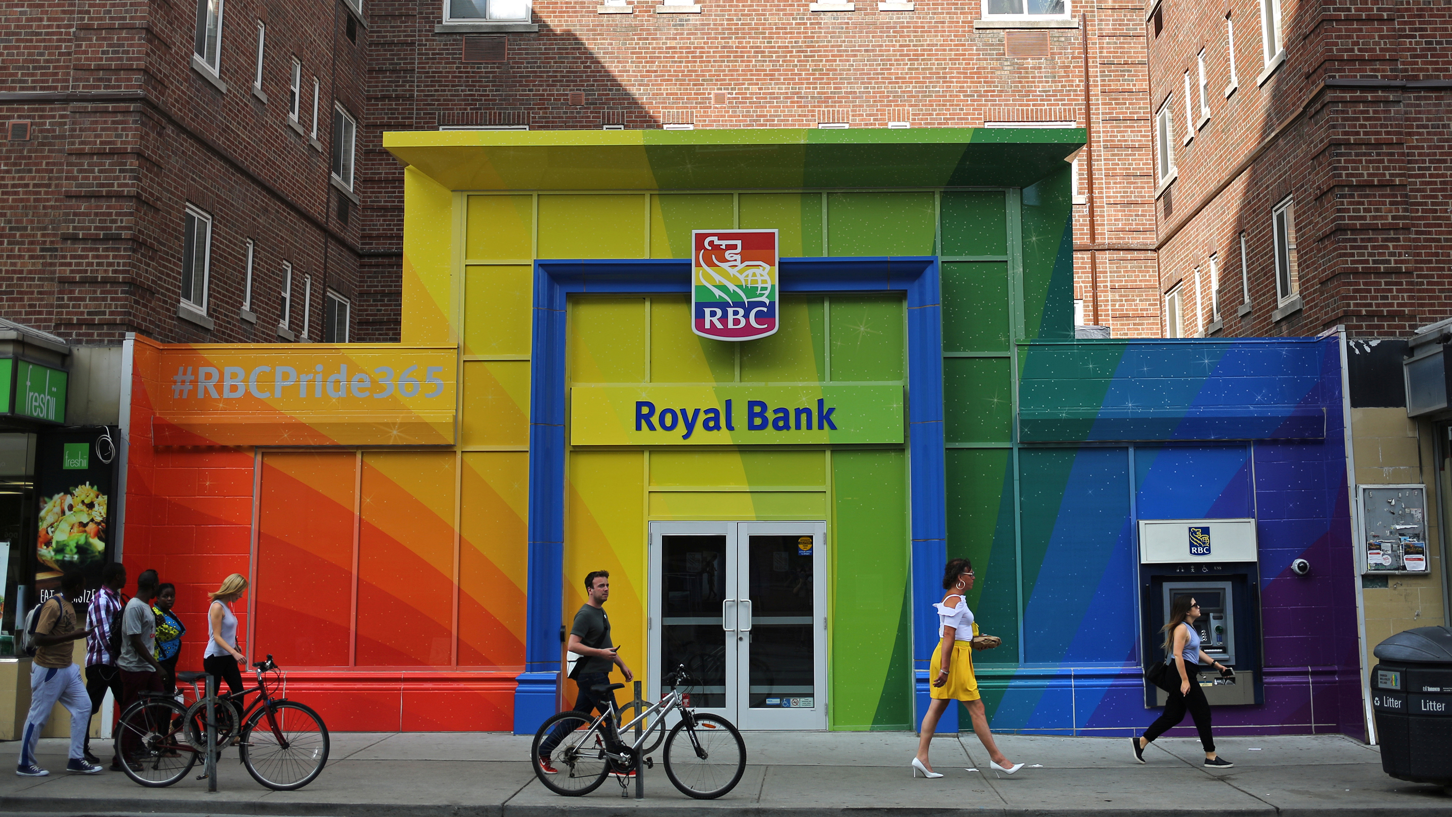 People pass an RBC branch adorned with colours of the Pride rainbow flag in downtown Toronto