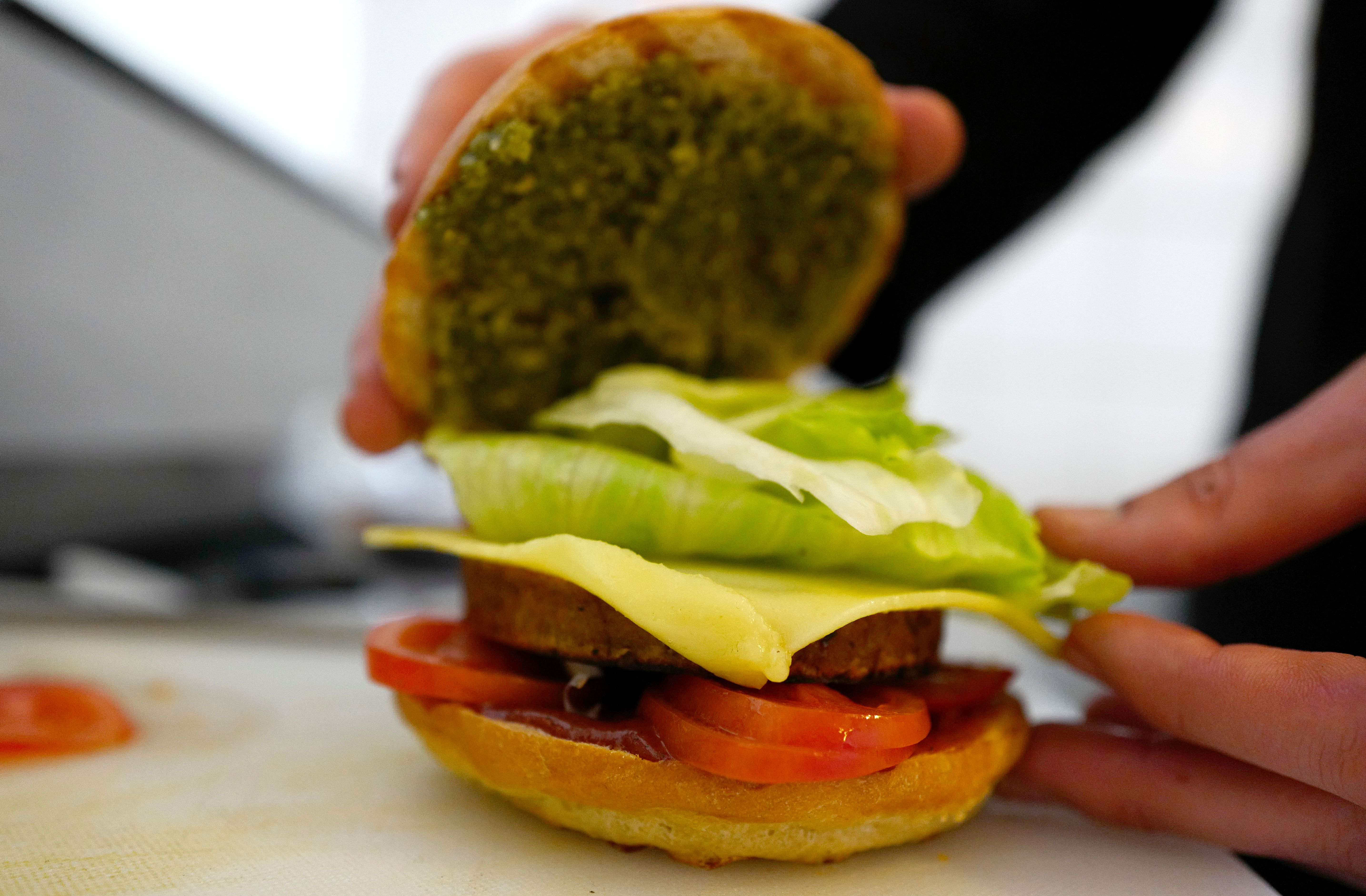 "Chef Johannes Thenerl prepares a vegan ""burger"" using a patty made of wild garlic (Baerlauch) at the vegan restaurant ""L'Herbivore"" in Berlin on April 29, 2016."