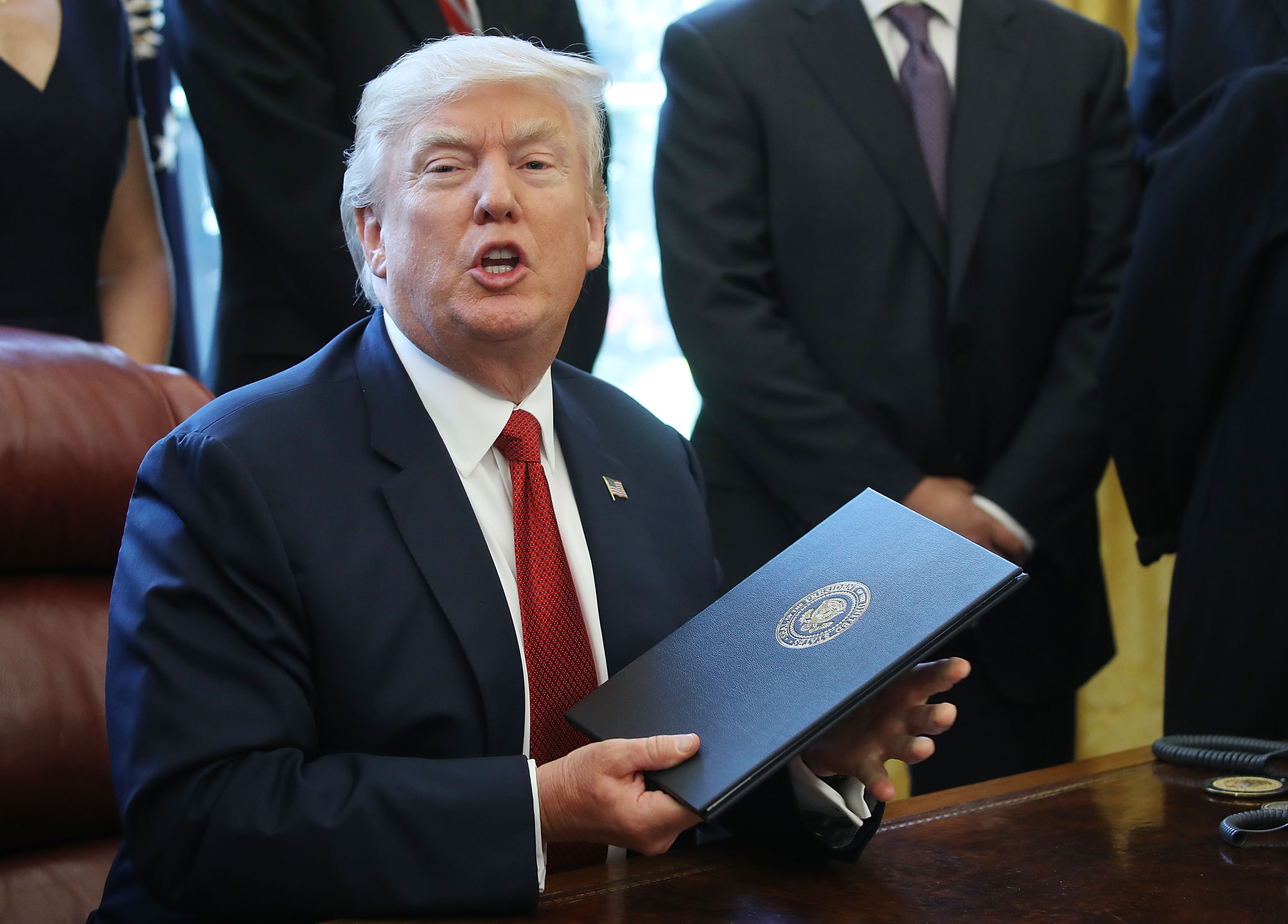 U.S. President Donald Trump holds up an Executive Memorandum on the investigation of steel imports, after signing it in the Oval Office at the White House, on April 20, 2017 in Washington, DC.