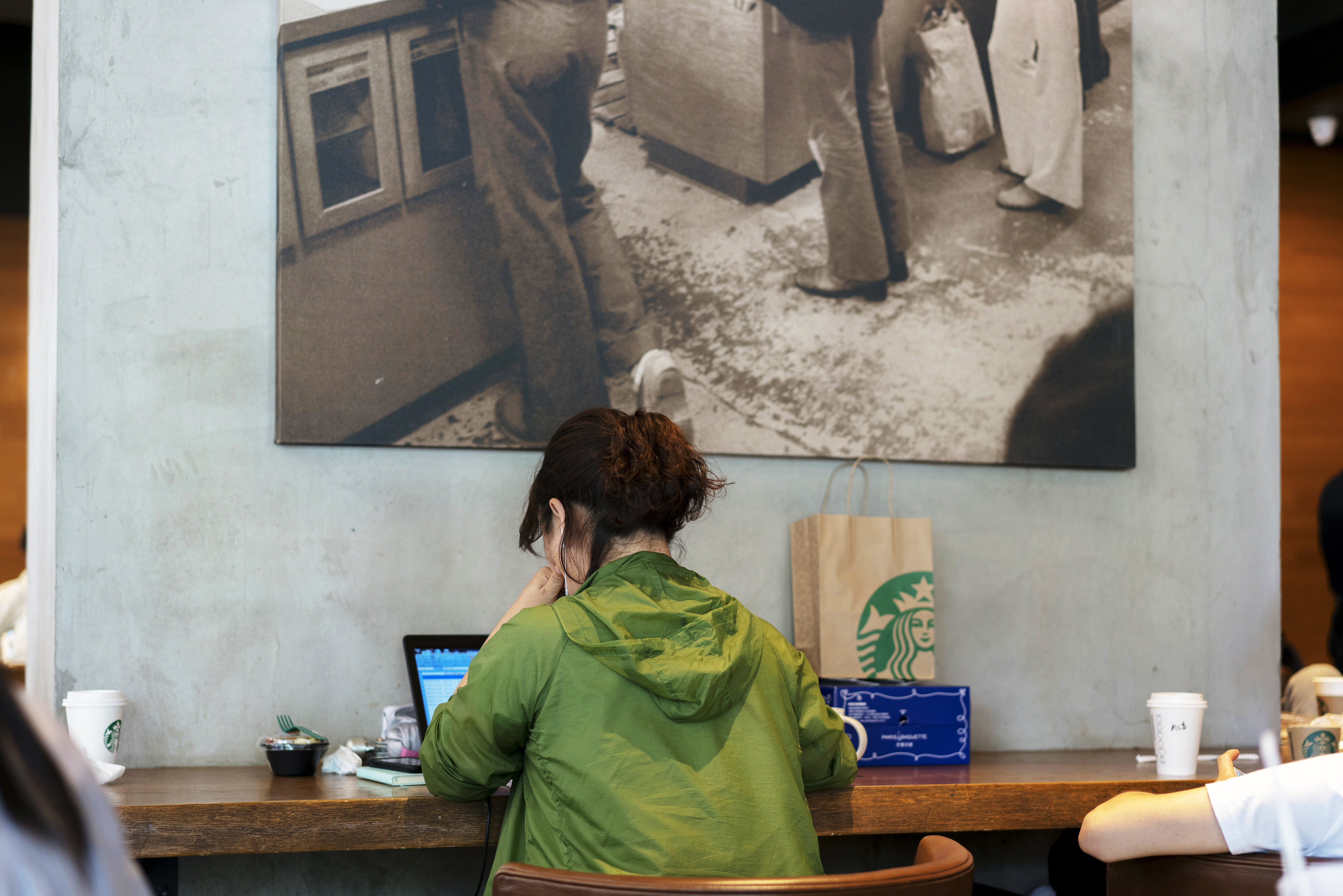 A girl is working on laptop in a Starbucks coffee shop. In