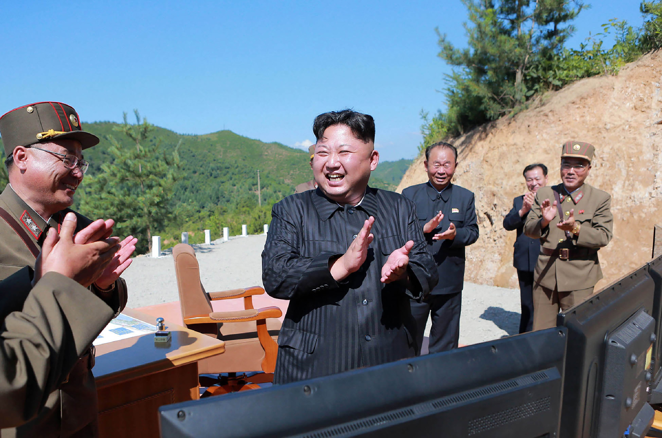 This picture taken on July 4, 2017 and released by North Korea's official Korean Central News Agency (KCNA) on July 5, 2017 shows North Korean leader Kim Jong-Un (C) celebrating the successful test-fire of the intercontinental ballistic missile Hwasong-14 at an undisclosed location.