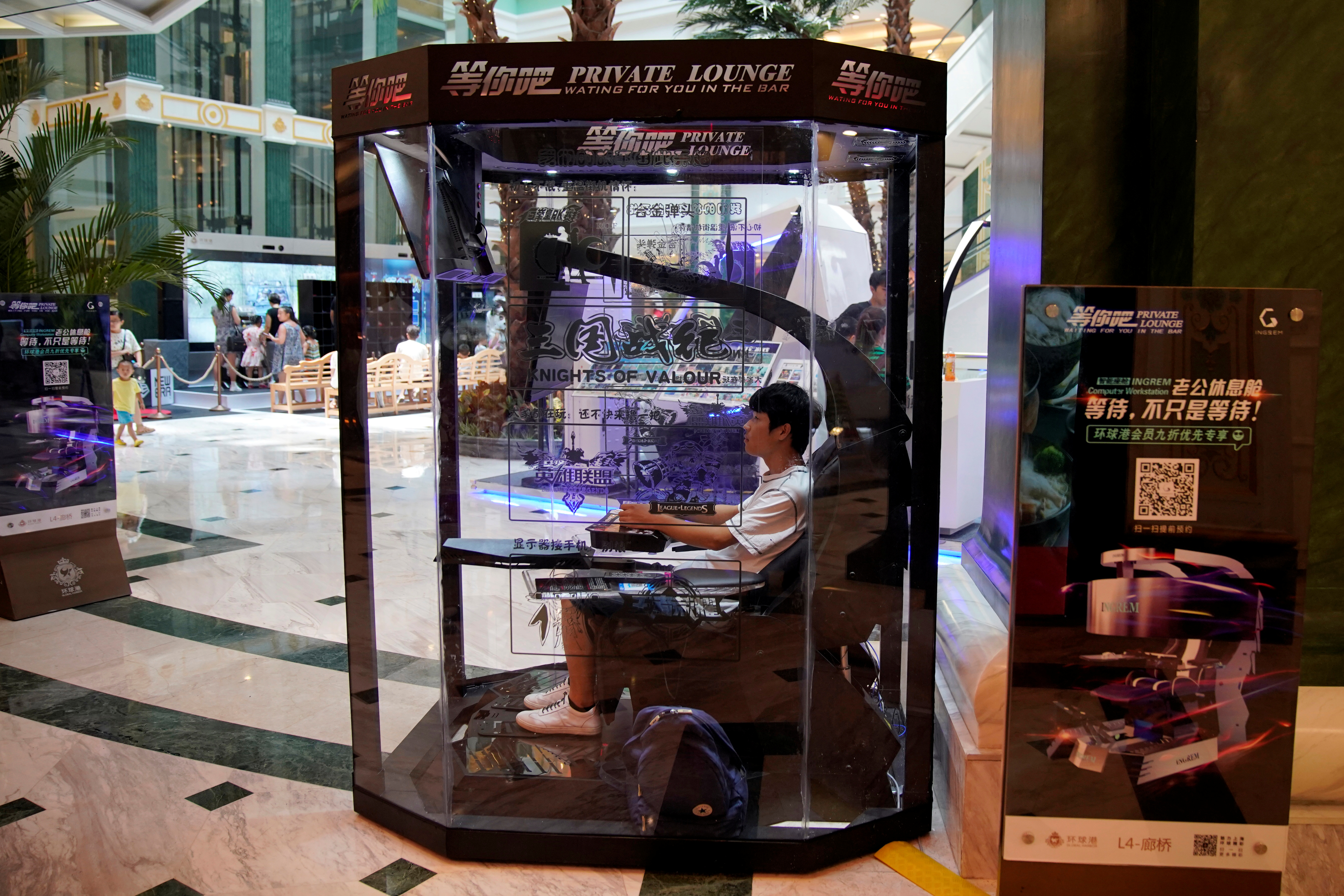 """An employee demonstrates a """"husband pod"""" at a shopping mall in Shanghai"""