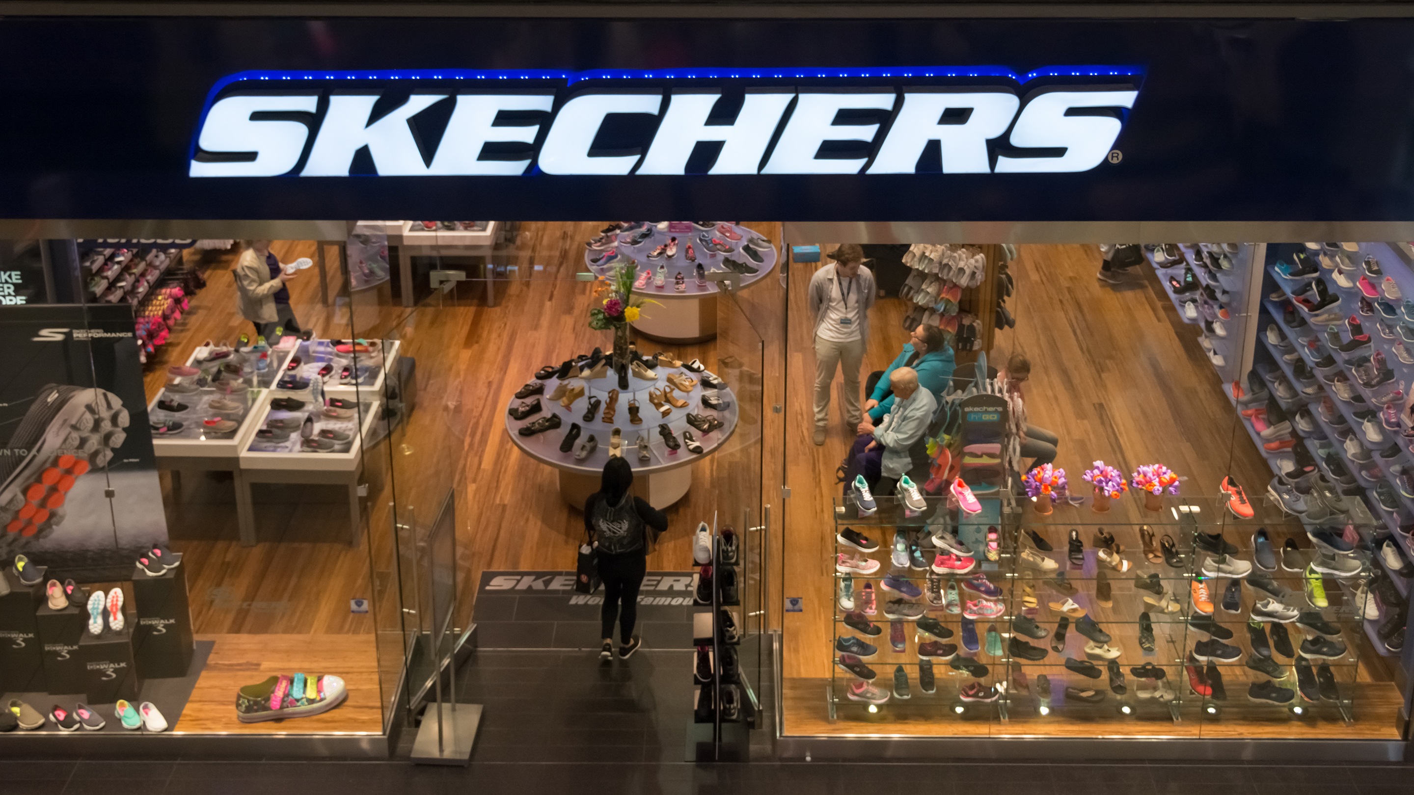 A woman enters Skechers shoe store looking for a good deal