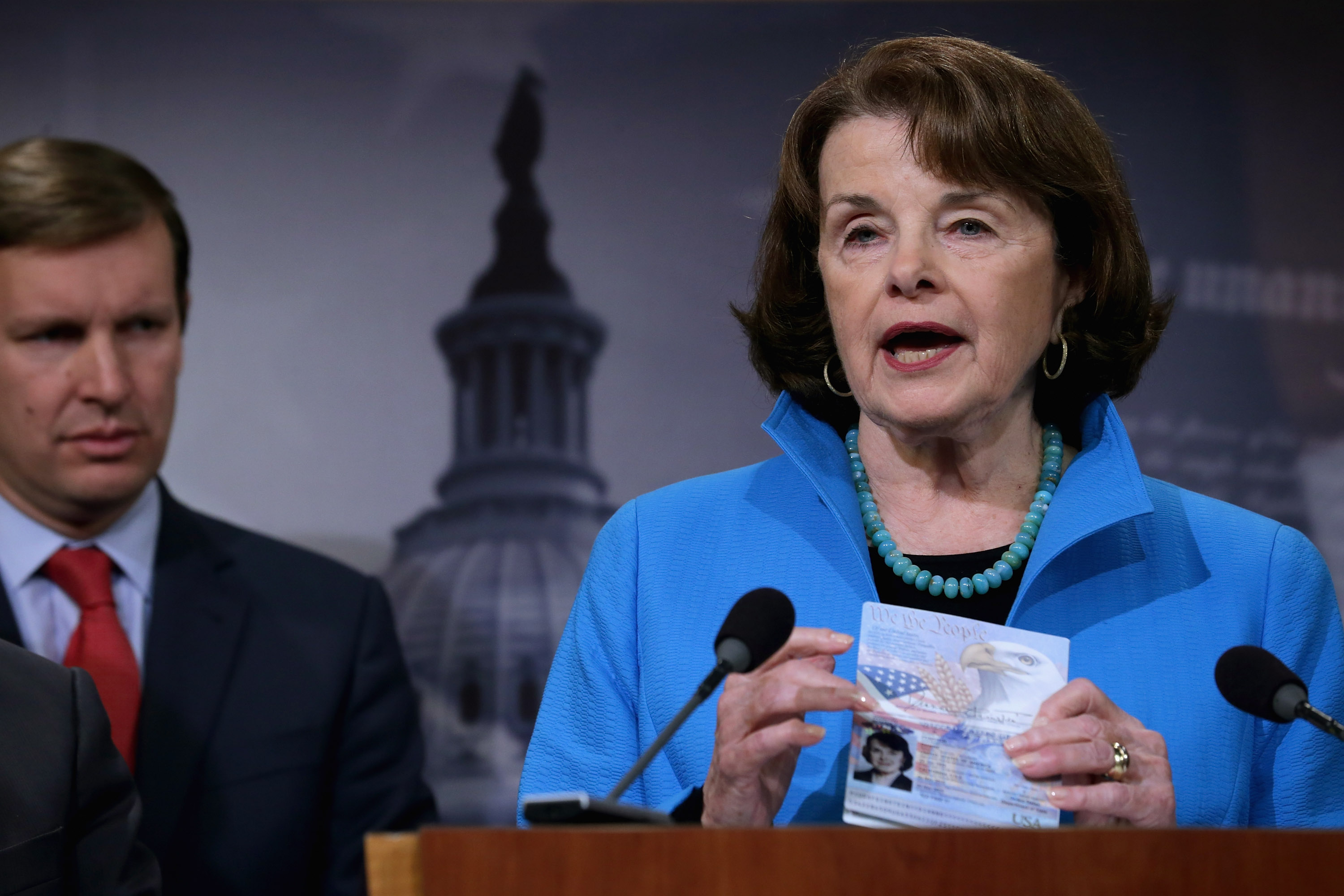 Senate Select Committee on Intelligence ranking member Sen. Dianne Feinstein (D-CA) (R) holds up her passport during a news conference about Democratic legislative proposals in the wake of last week's terror attacks in Paris with Sen. Chris Murphy (D-CT) at the U.S. Capitol November 19, 2015 in Washington, DC.