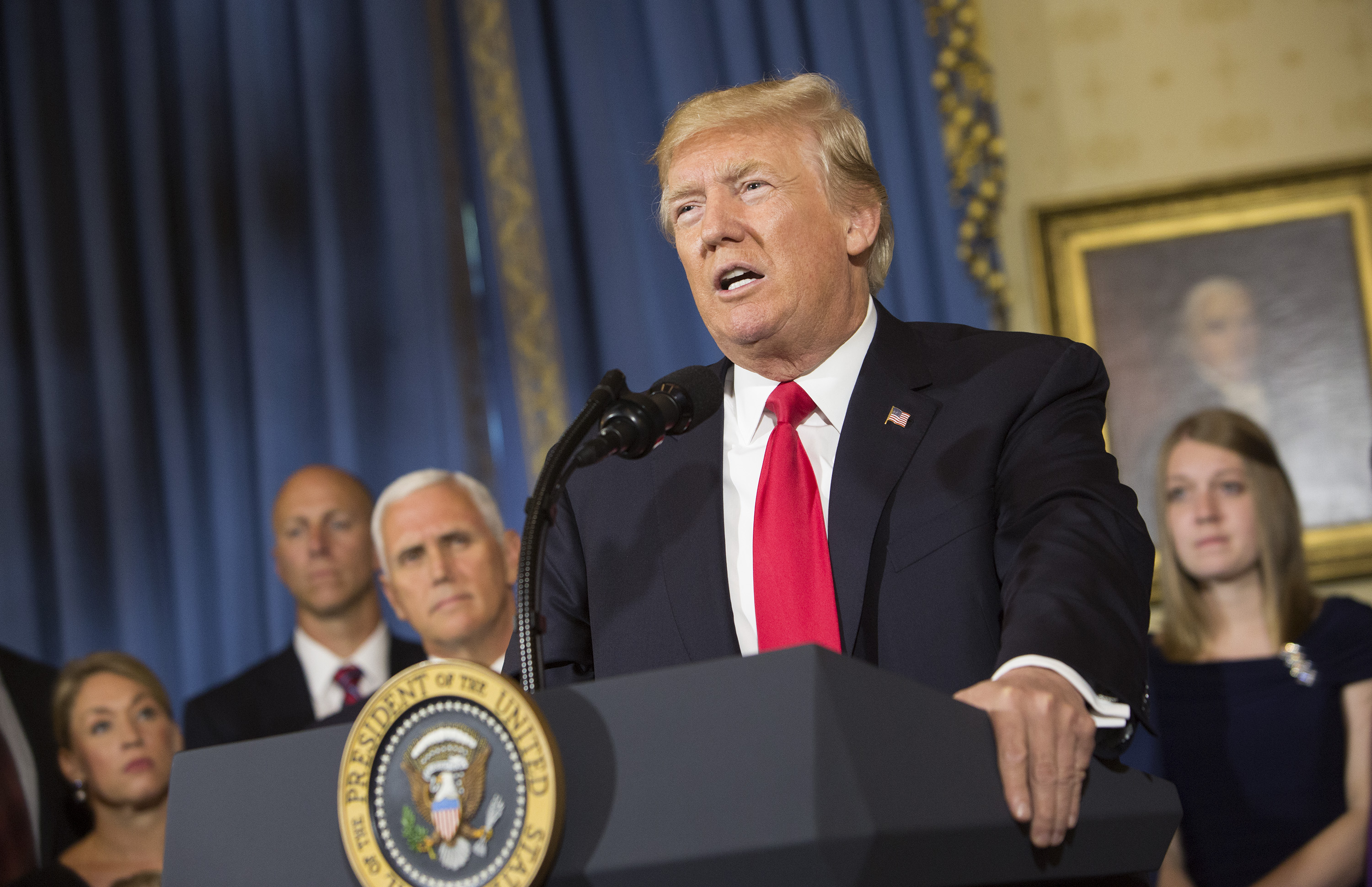 """U.S. President Donald Trump makes a statement on health care while standing with """"victims of Obamacare"""" at The White House on July 24, 2017 in Washington, DC."""