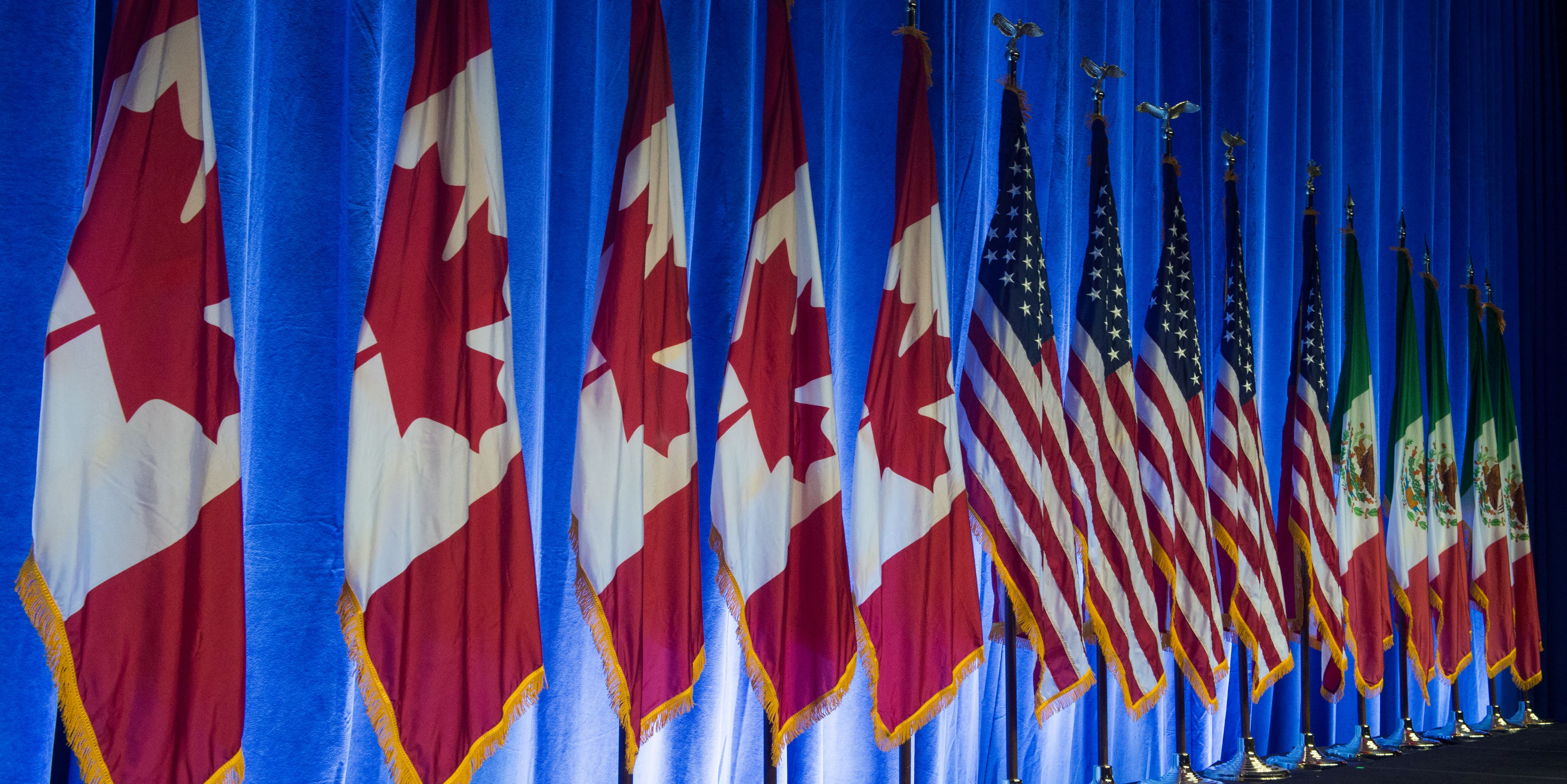 The flags of Canada, the United States, and Mexico, line the stage before the start of the negotiations for the modernization of NAFTA, August 16, 2016, in Washington, DC.
