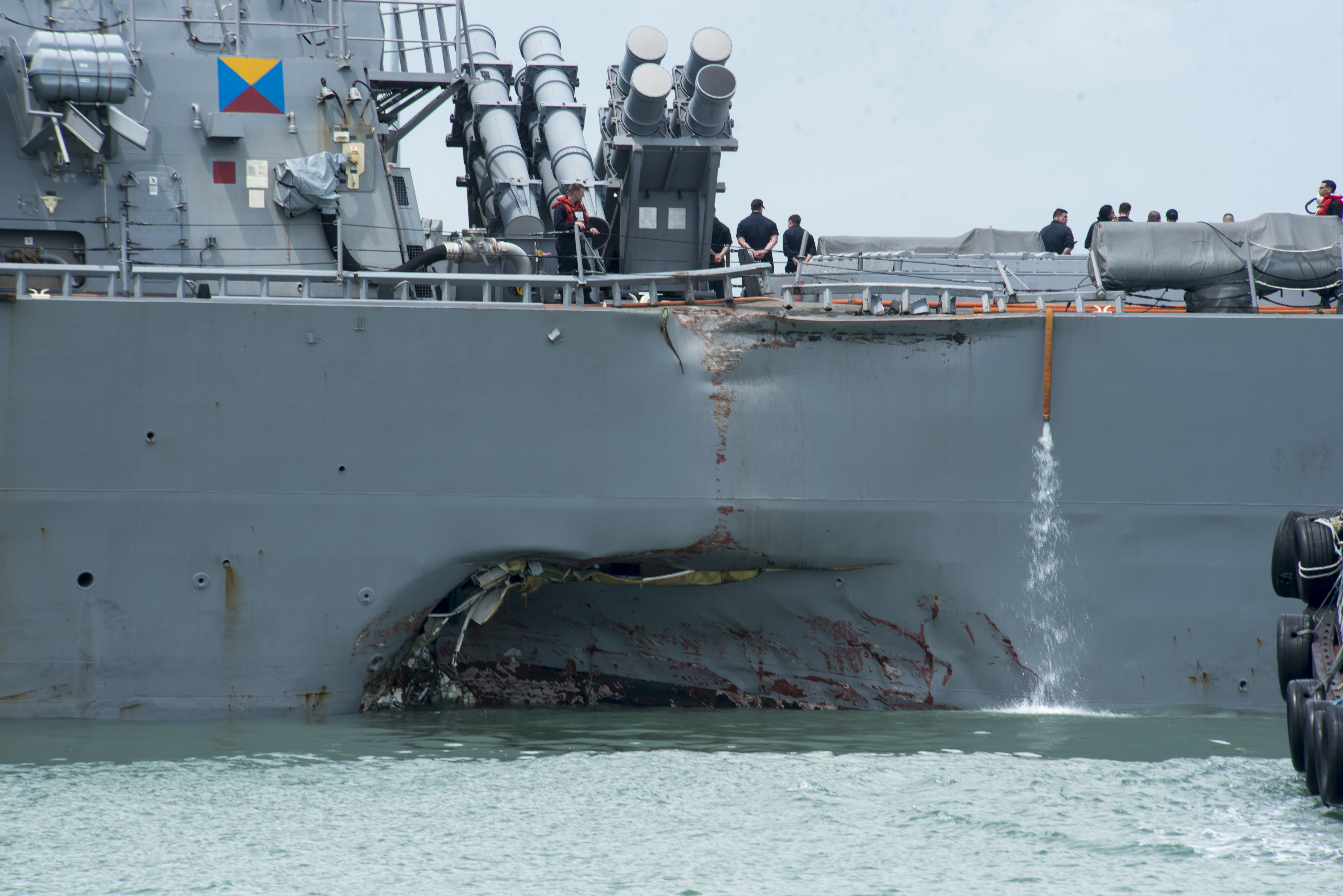 In this released U.S. Navy handout, damage to the portside is visible as the Guided-missile destroyer USS John S. McCain (DDG 56) steers towards Changi Naval Base, Republic of Singapore, following a collision with the merchant vessel Alnic MC while underway east of the Straits of Malacca and Singapore on Aug. 21.