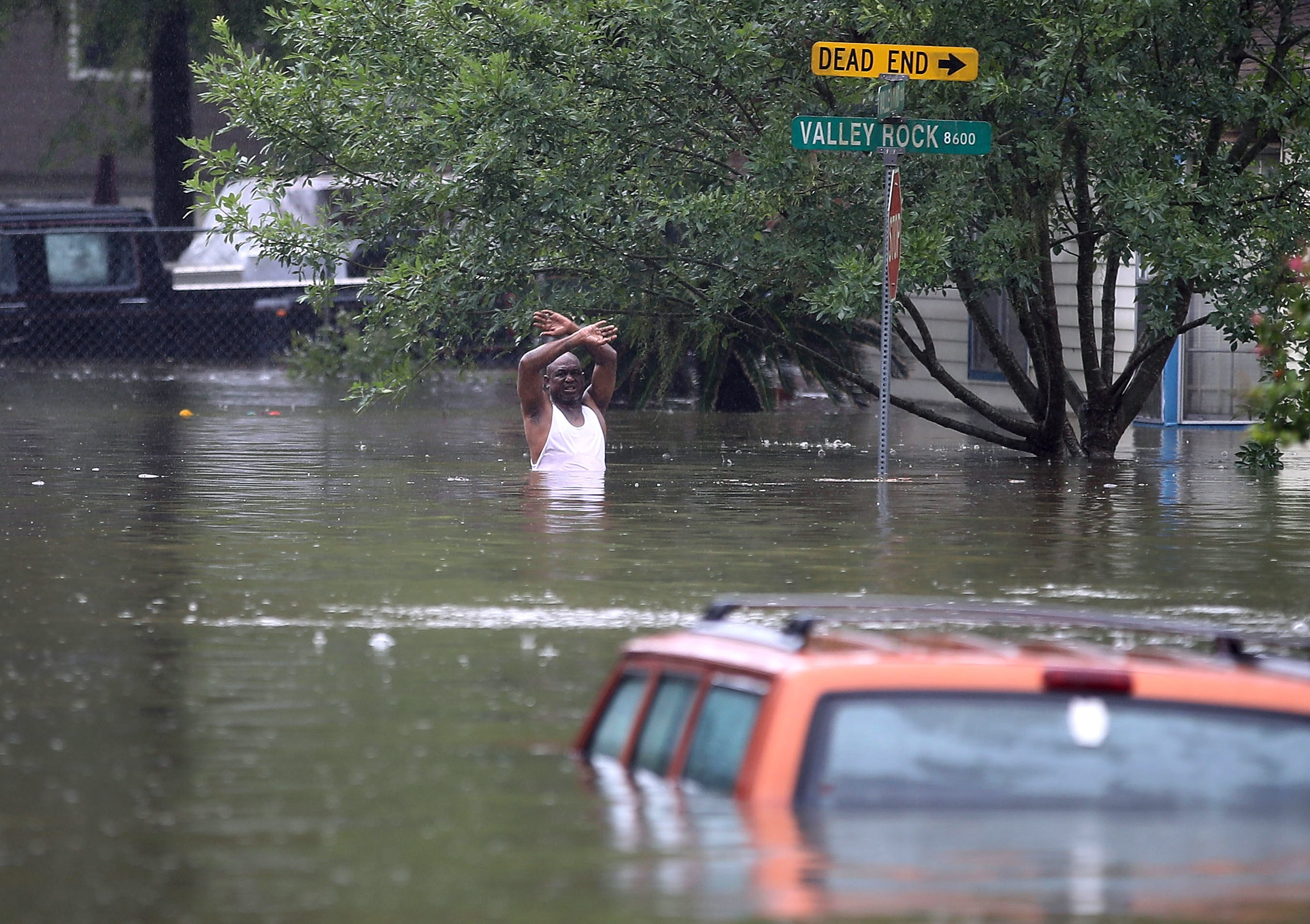 A man waves down a rescue crew as he tries to leave the area after it was inundated with flooding from Hurricane Harvey on August 28, 2017 in Houston, Texas. Harvey, which made landfall north of Corpus Christi late Friday evening, is expected to dump upwards to 40 inches of rain in Texas over the next couple of days.