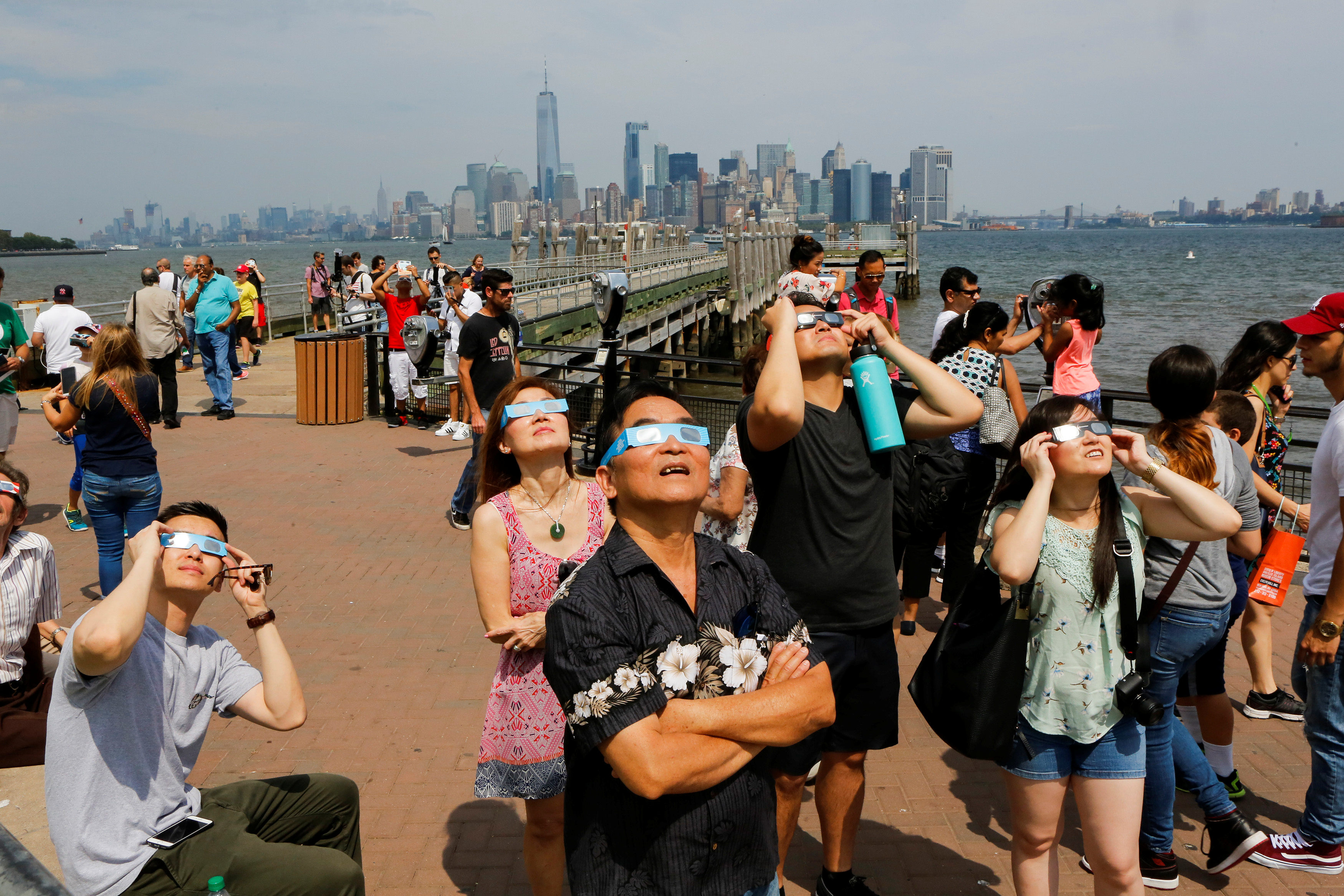 People view the solar eclipse at Liberty State Island as the Lower Manhattan and One World Trade center are seen in the background in New York
