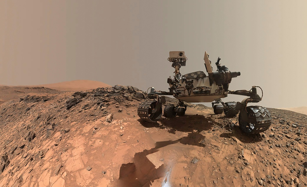 NASA's Curiosity Mars rover is seen at the site from which it reached down to drill into a rock target called 'Buckskin' on lower Mount Sharp