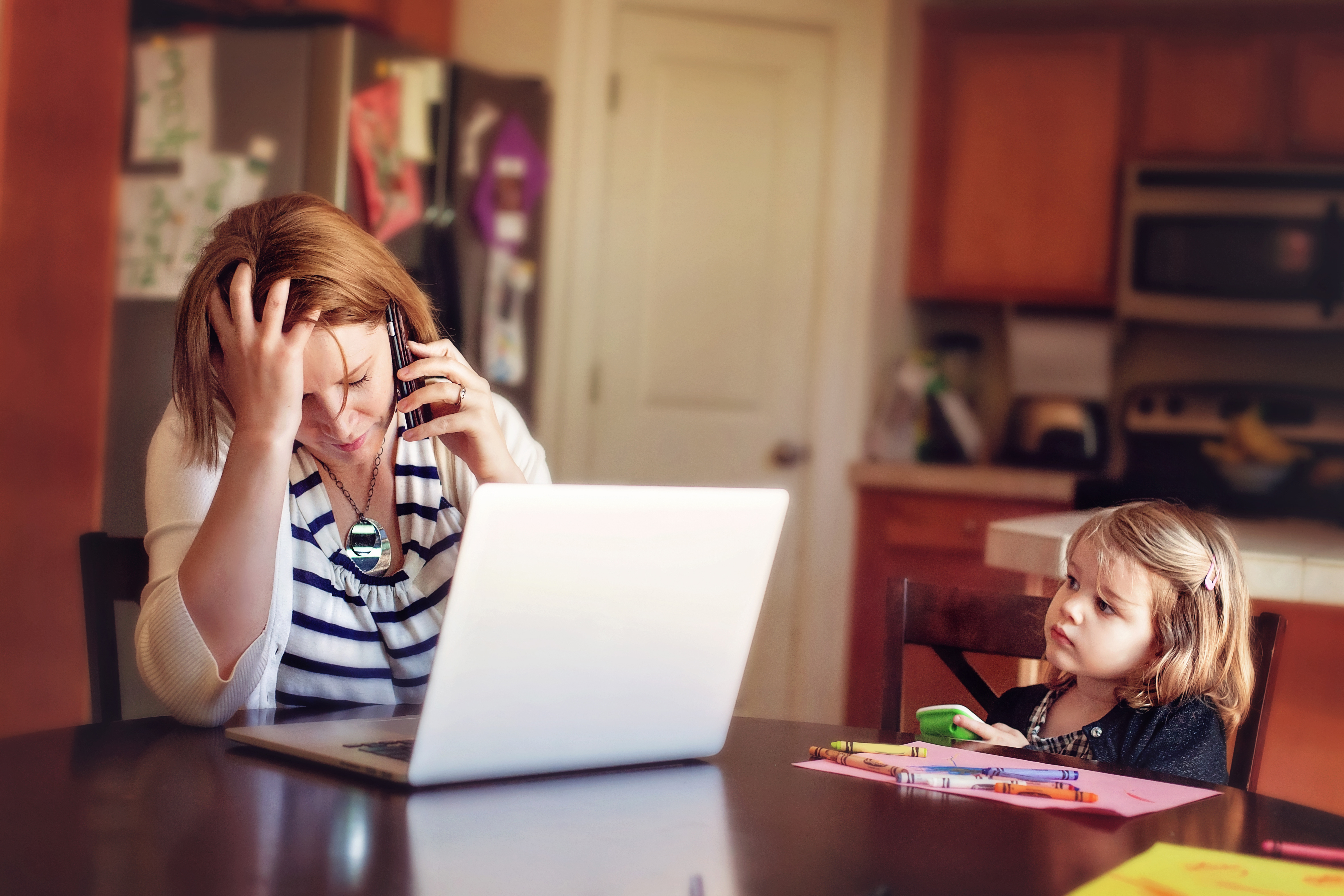Woman frustrated at computer while daughter watches concerned