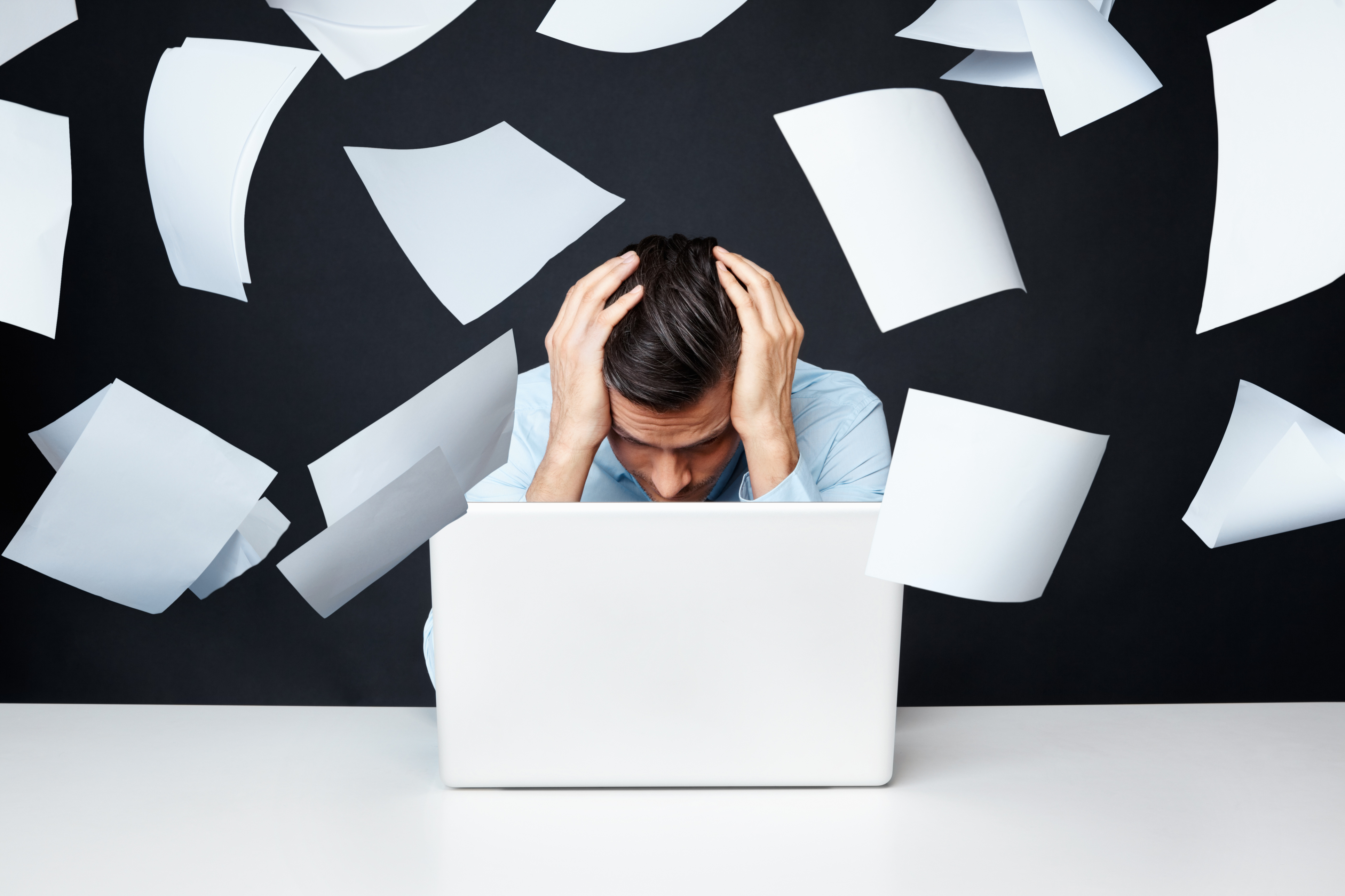Man with hand on head looking at laptop with papers flying