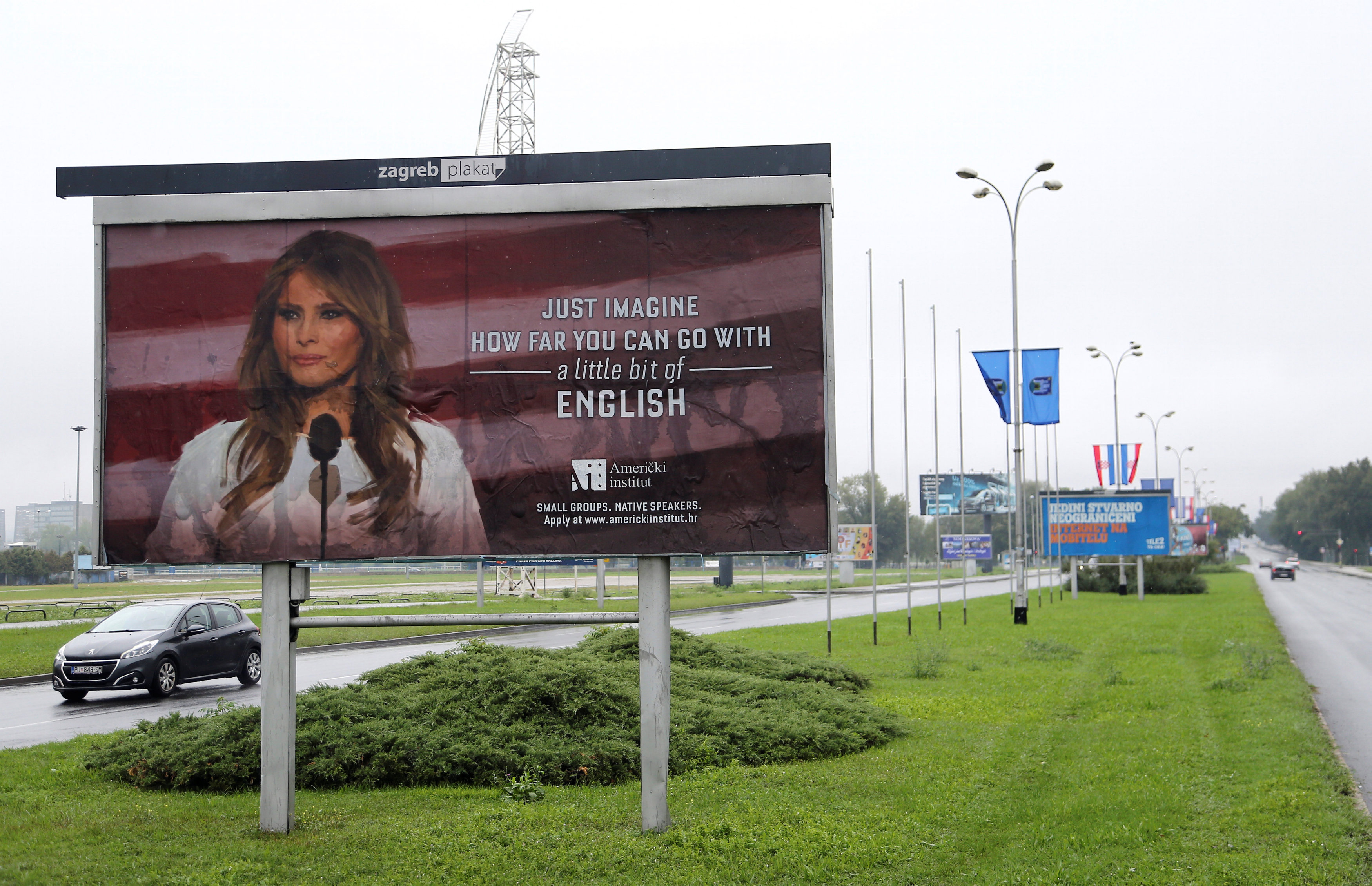 Cars drive near a billboard advertising a language school with the image of U.S. first lady Melania Trump in Zagreb, Croatia