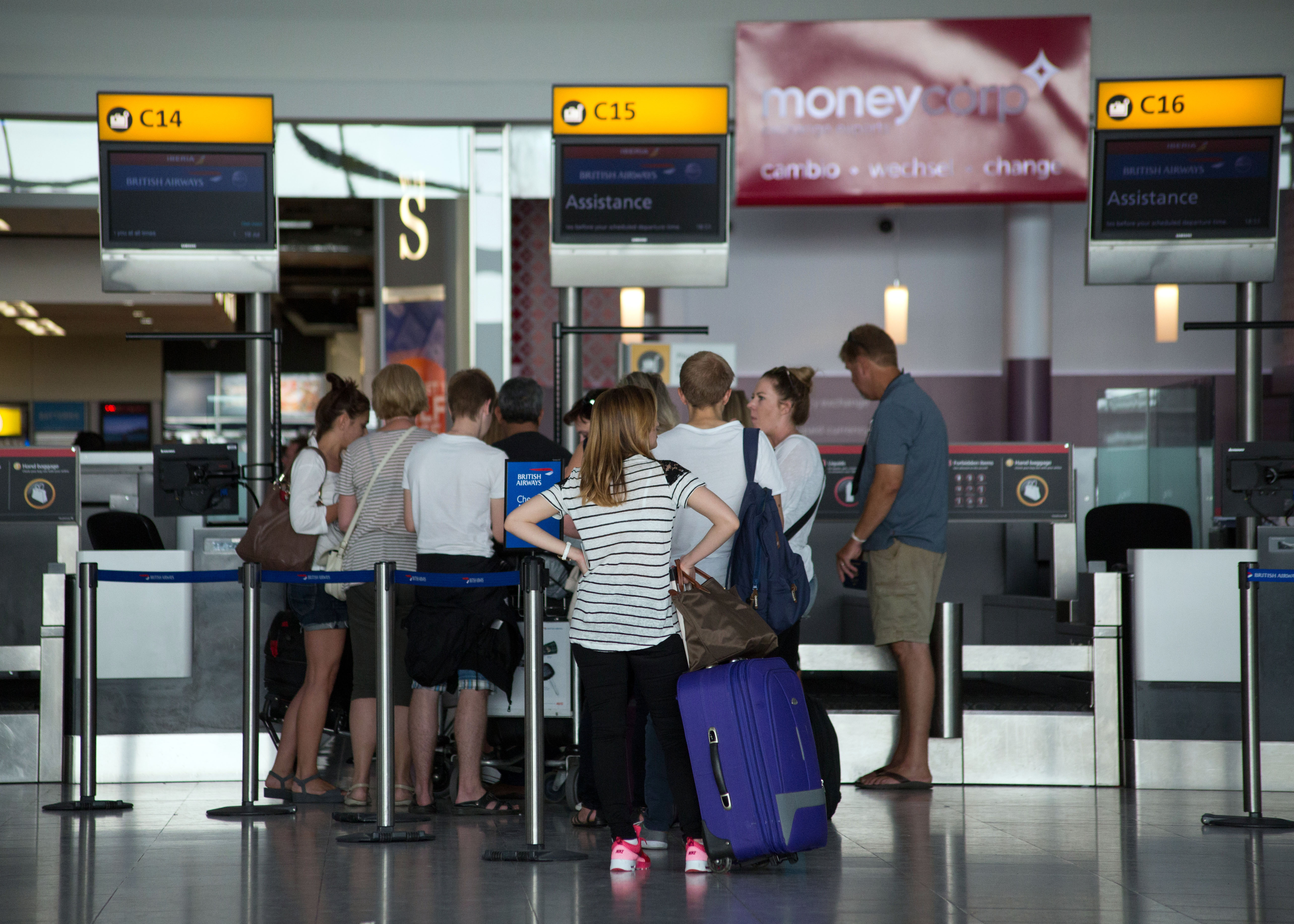 Passengers queues to drop their bags off as they check-in for their flights in Terminal 5 of Heathrow Airport.