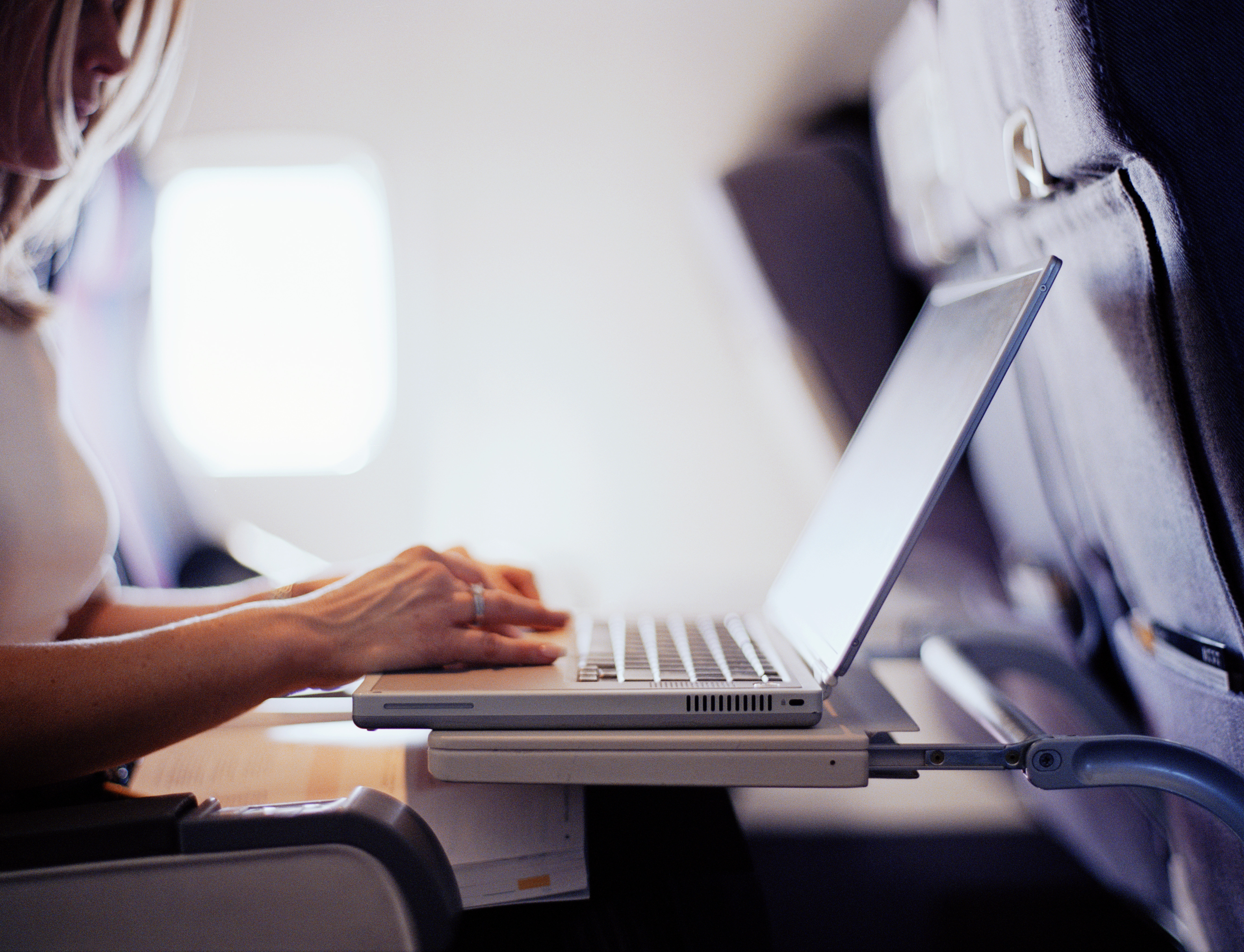 Woman typing on laptop computer in commercial airplane