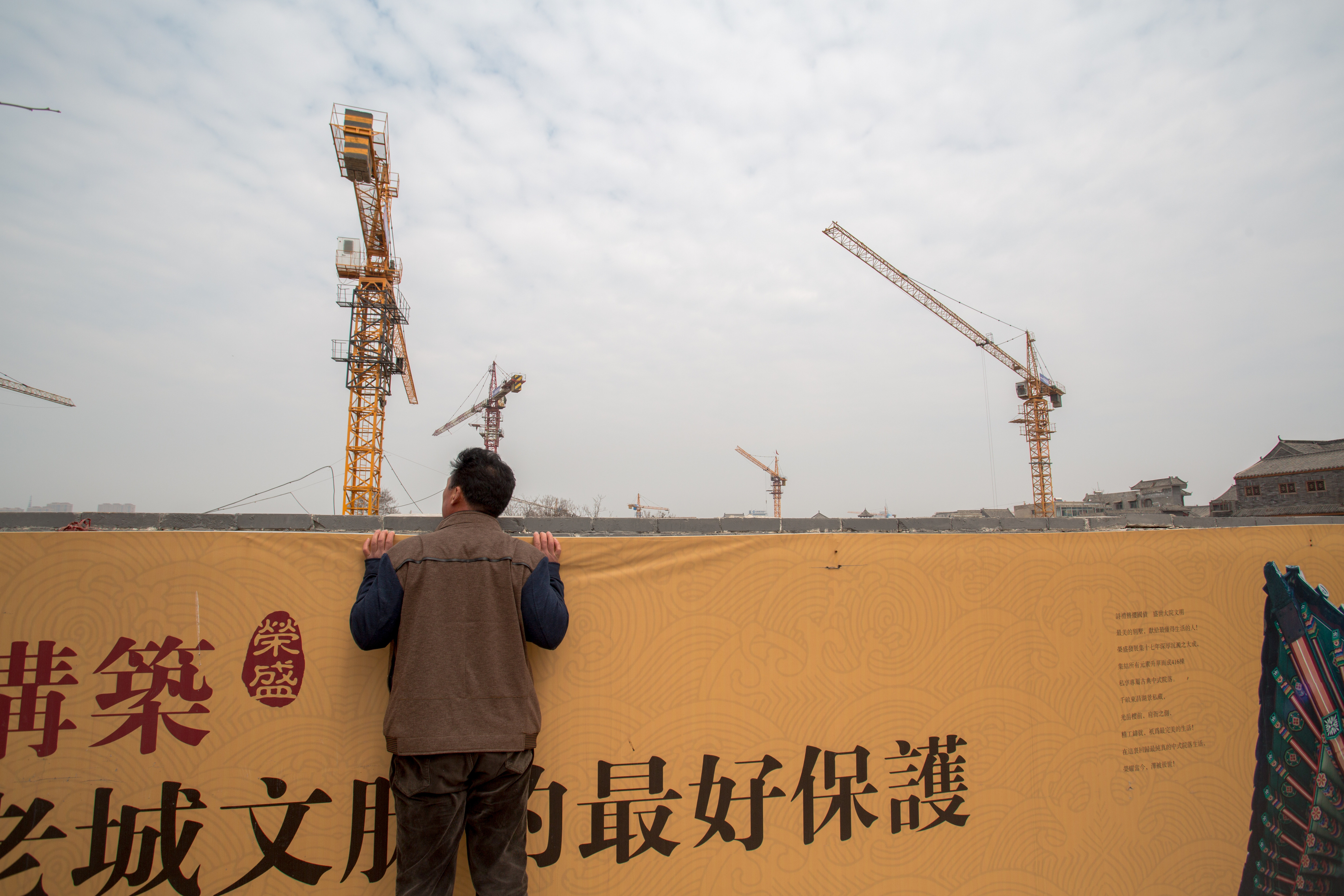 Pedestrian looks into a construction site of a high-end