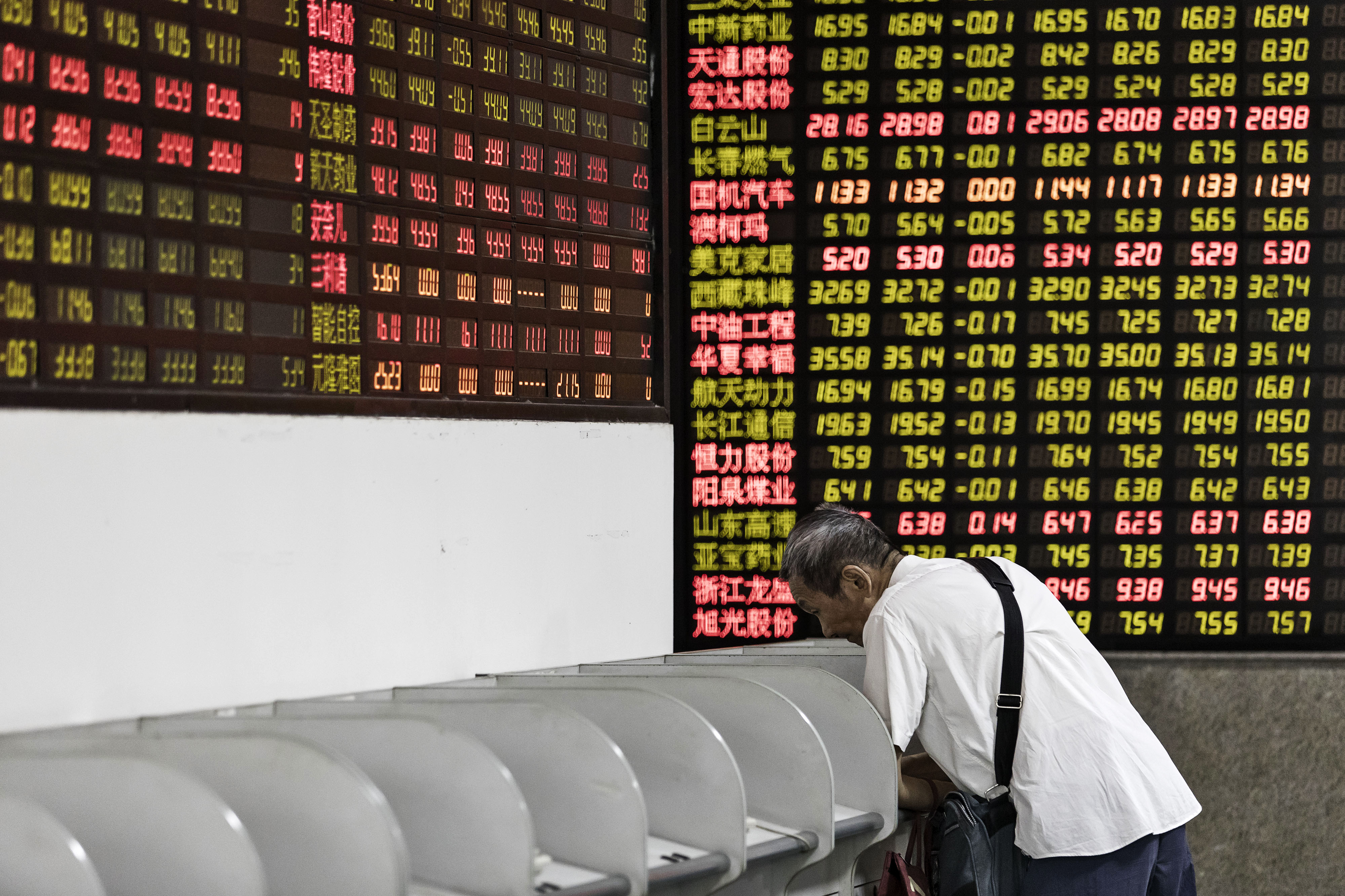 Investors Watch Stock Boards At A Security Firm