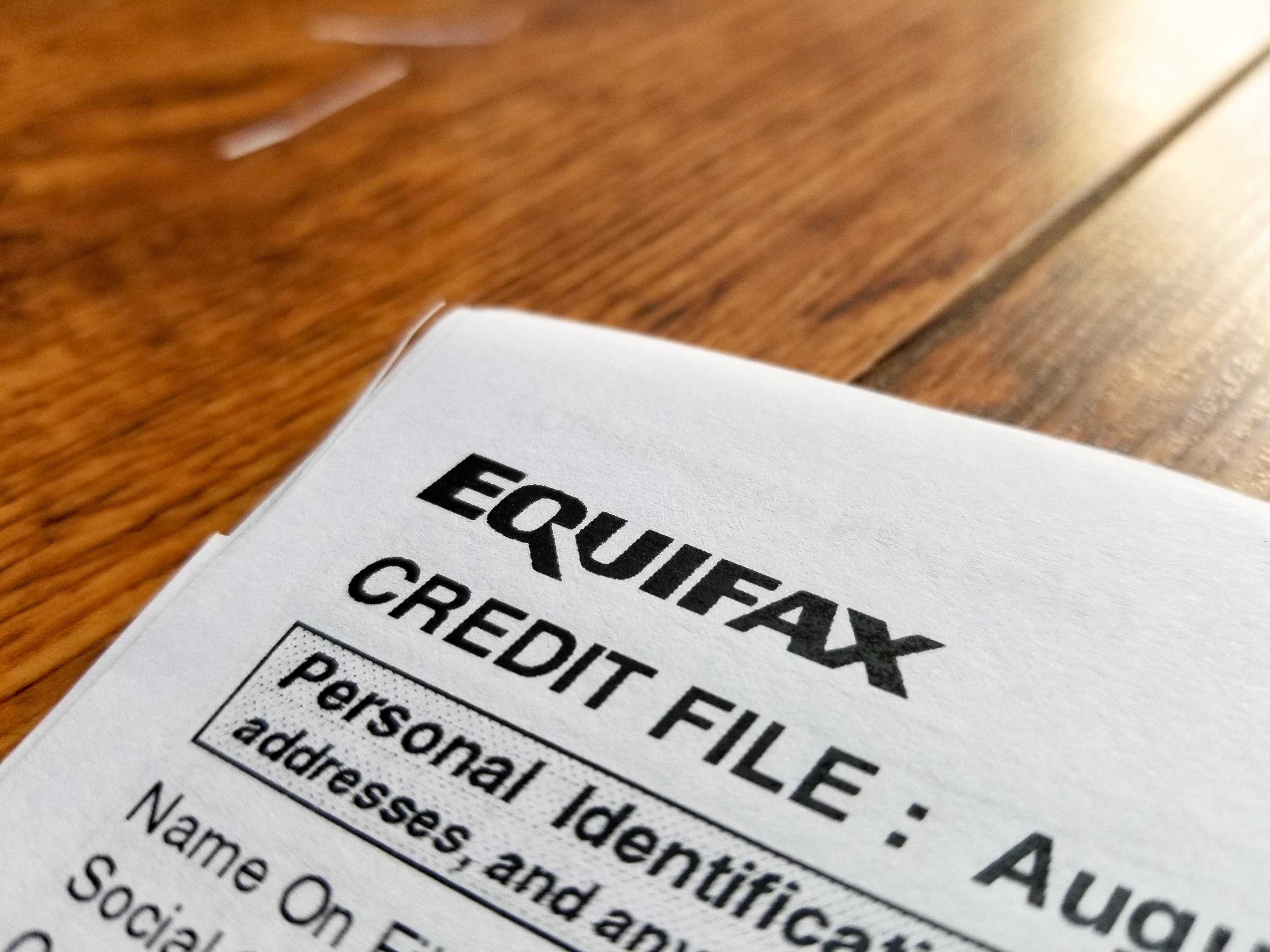 Close-up of the upper corner of a consumer credit report from the credit bureau Equifax, with text reading Credit File and Personal Identification, on a light wooden surface, September 11, 2017.