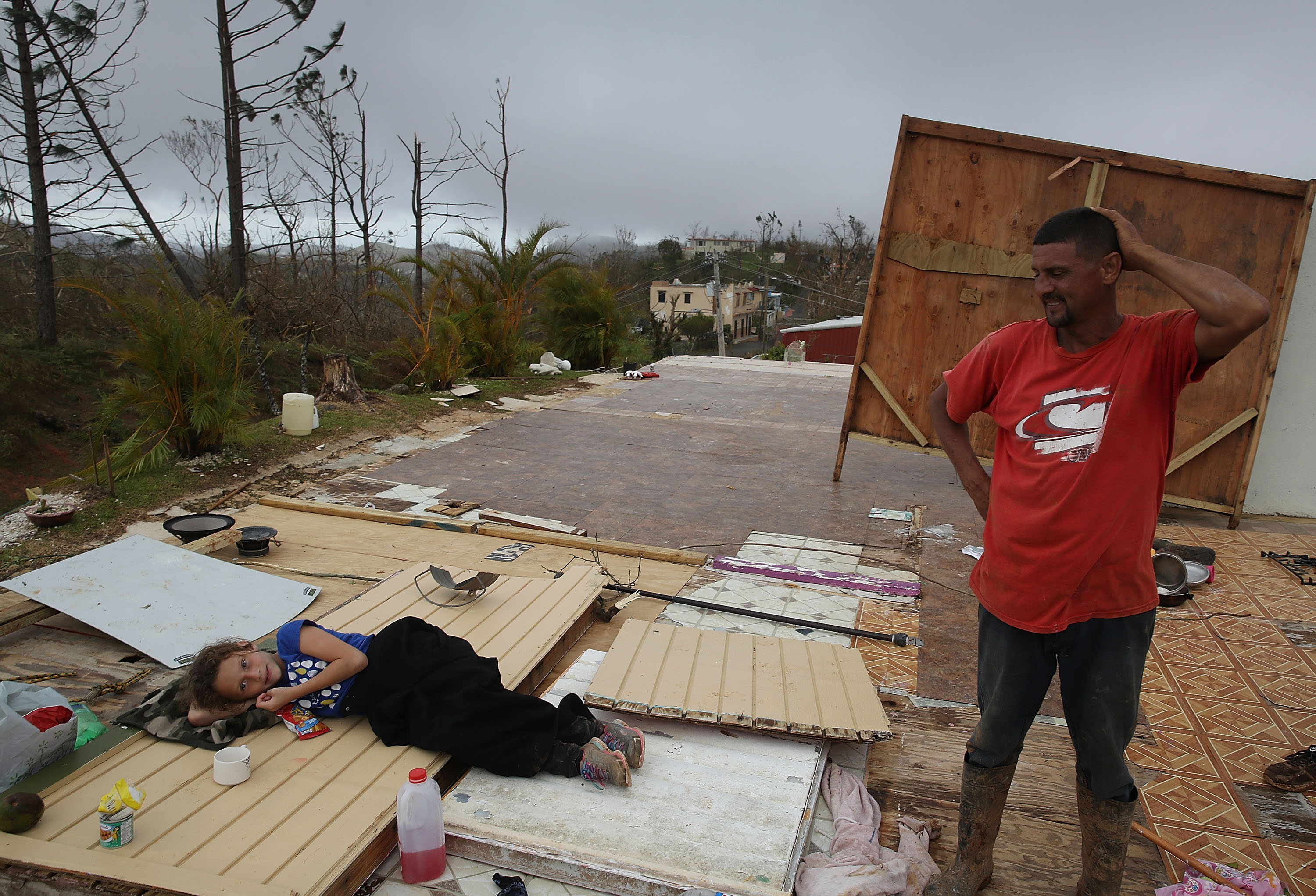 Karlian Mercado,7, and her father Carlos Flores stand on what remains of their home September 24, 2017 in Hayales de Coamo, Puerto Rico.