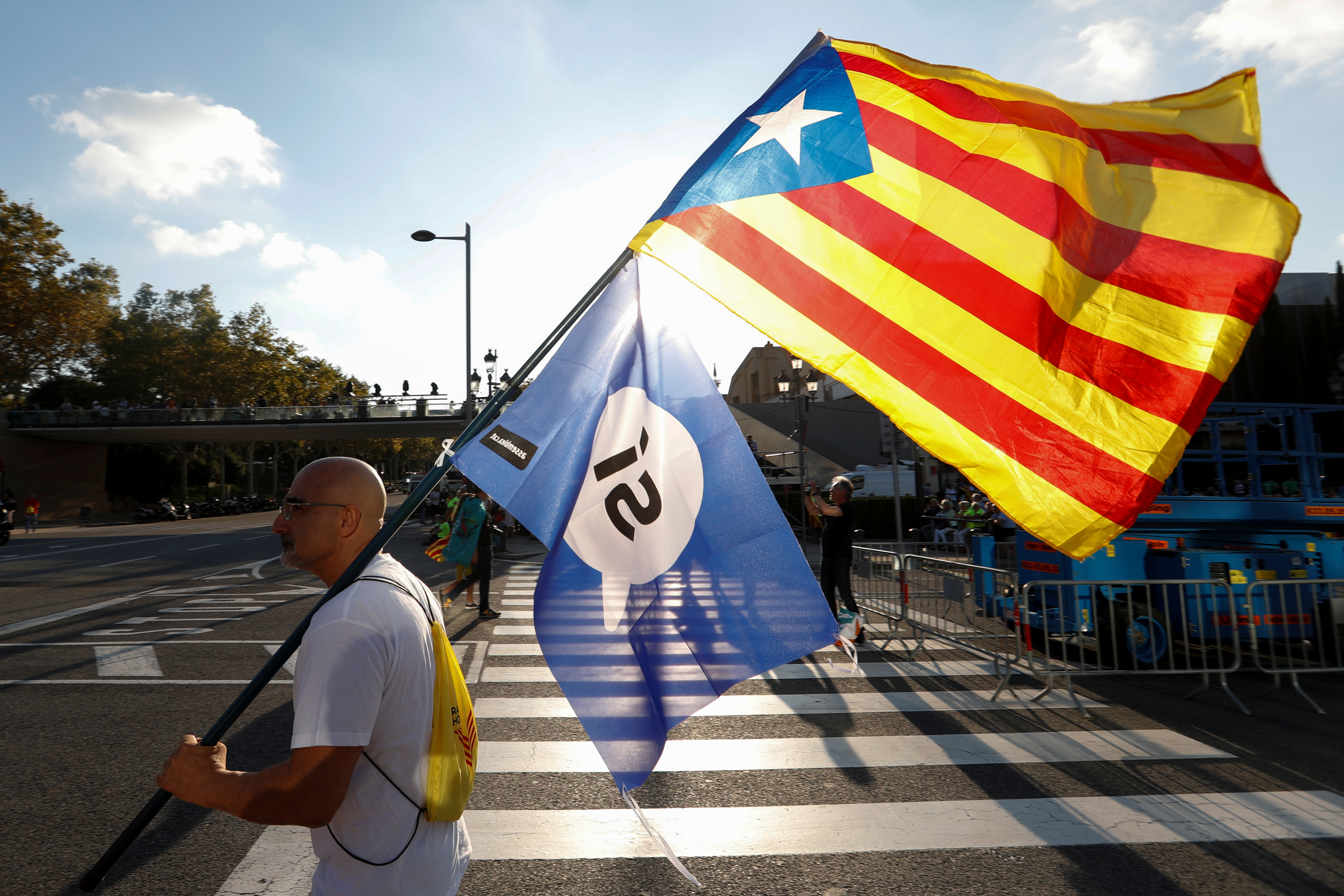 A man holds an Estelada (Separatist Catalan flag) and a pro-referendum flag as he arrives at a closing rally in favour of the banned October 1 independence referendum in Barcelona