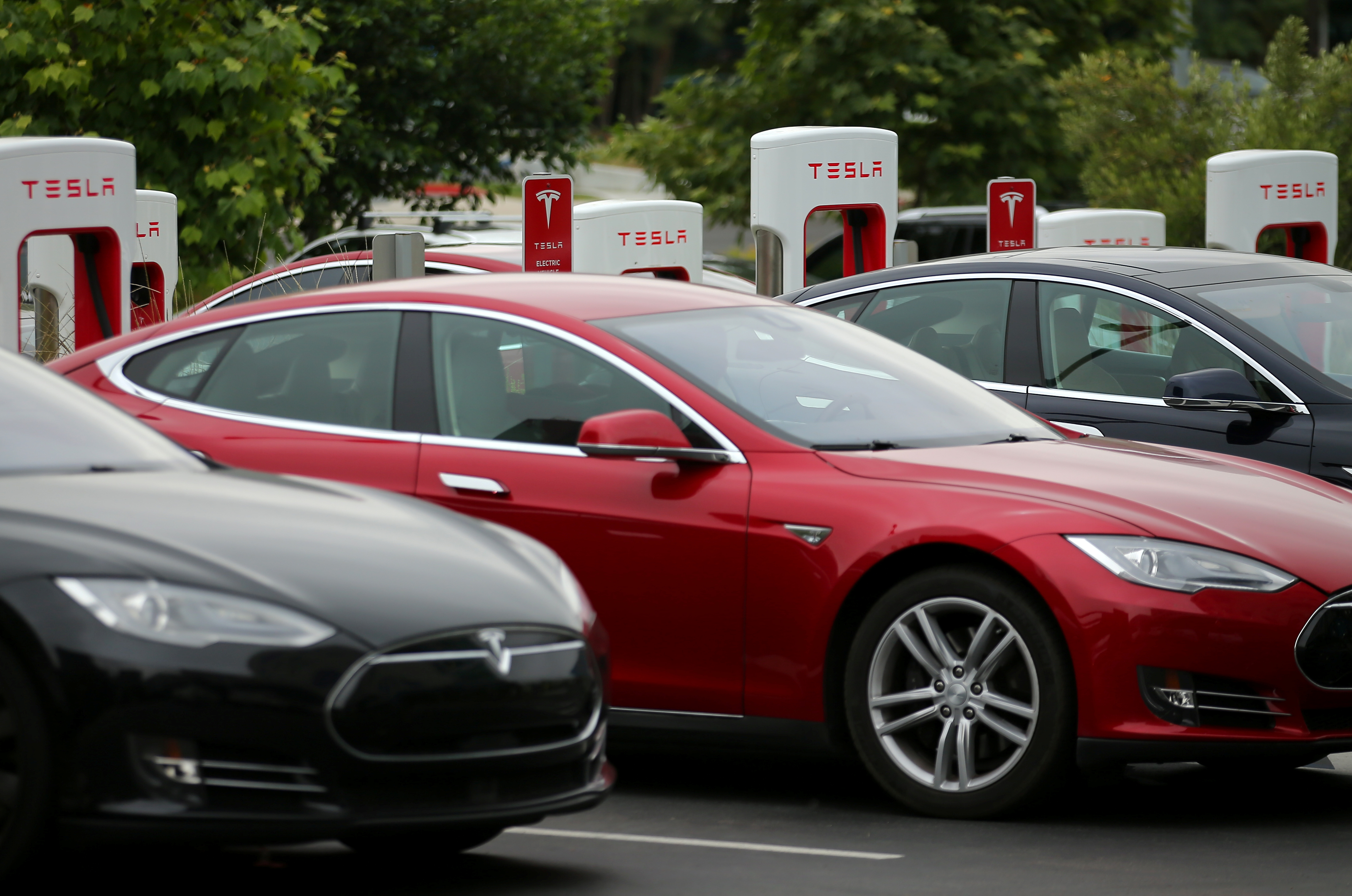 Tesla vehicles charge at a Tesla Supercharger station on the Qualcomm campus in San Diego