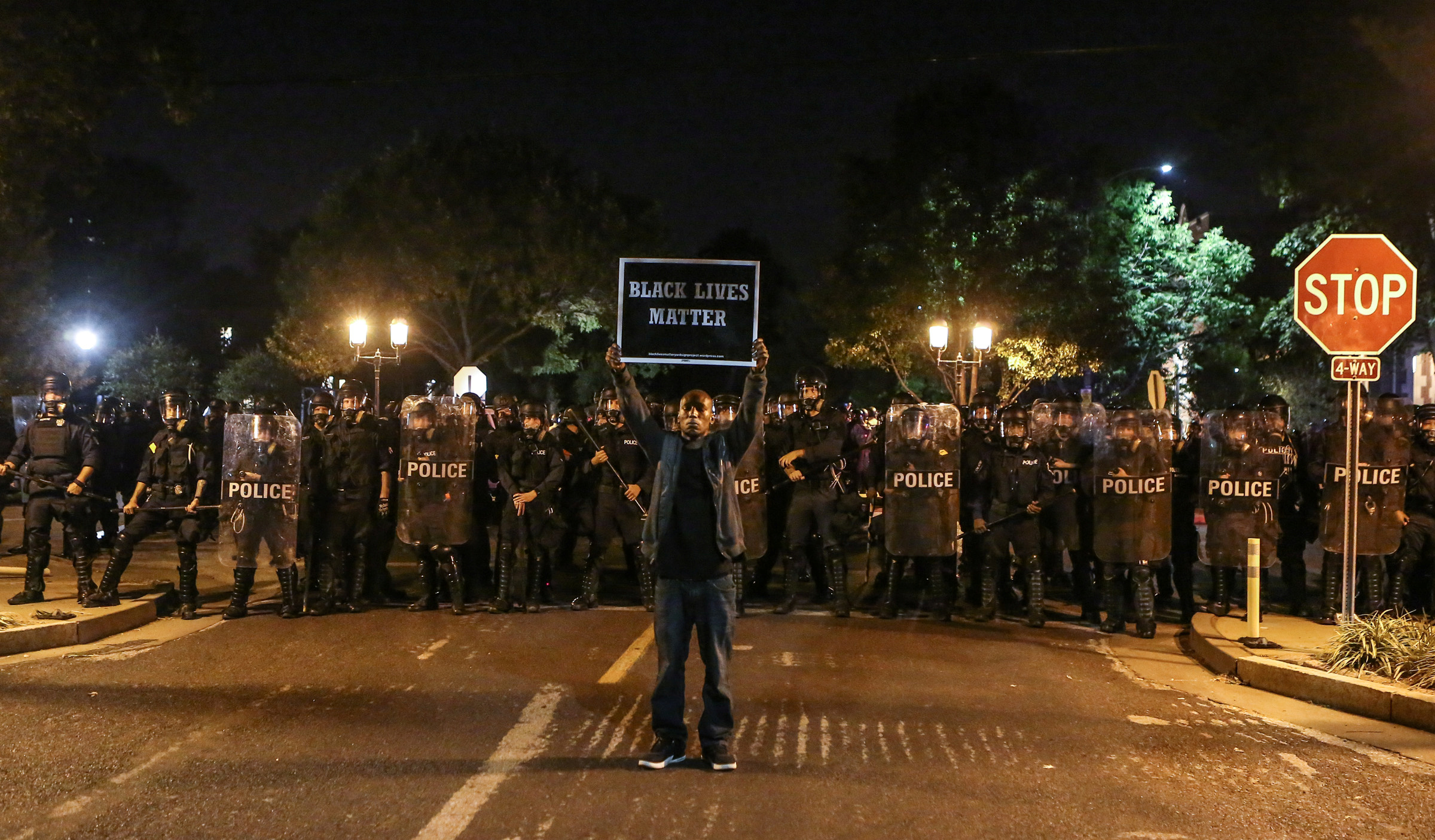 A Black Lives Matter protester stands in front of St. Louis Police Department officers equipped with riot gear in St. Louis