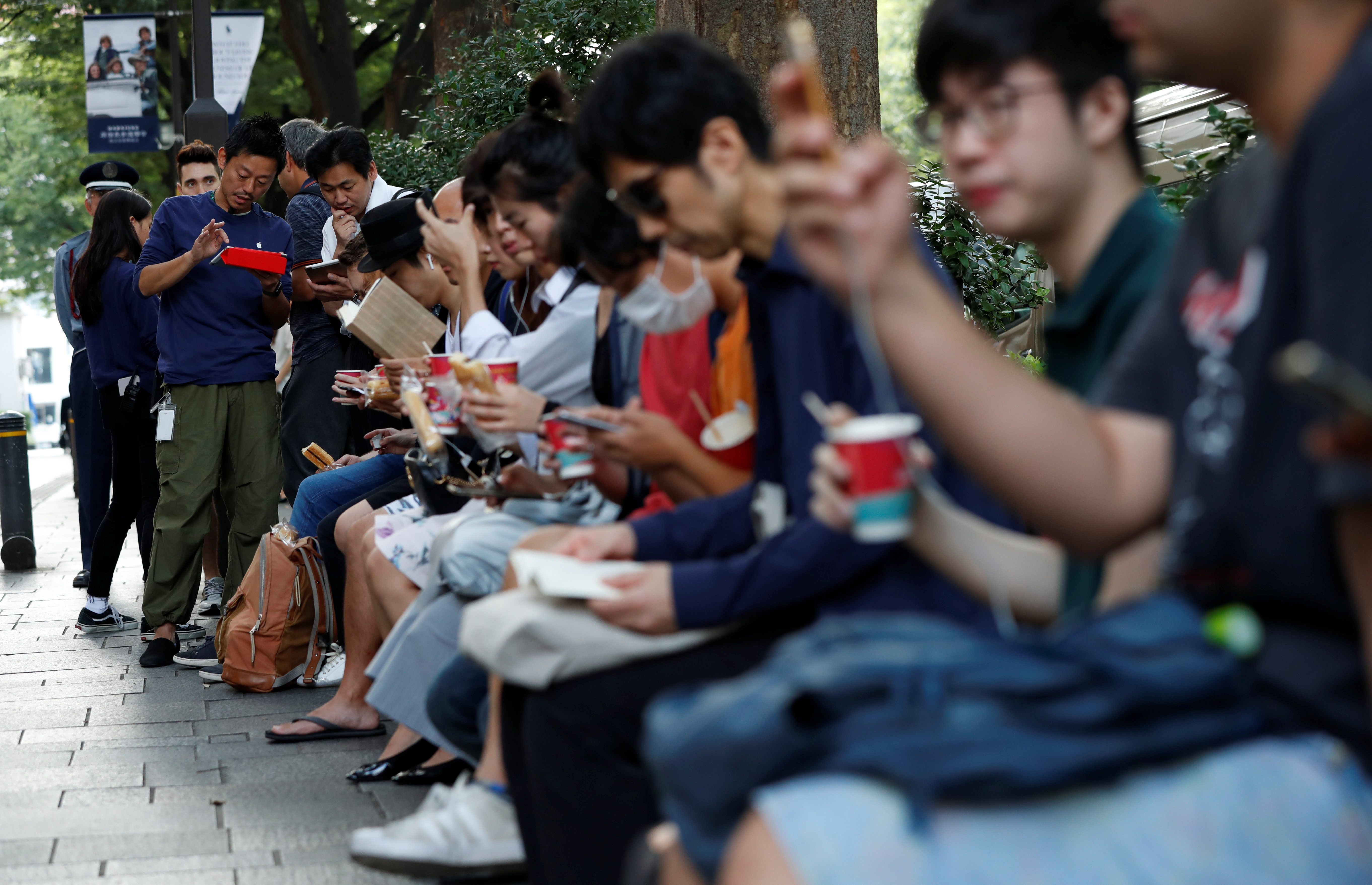 Customers sit in queue for the release of Apple's new iPhone 8 and 8 Plus outside the Apple Store in Tokyo's Omotesando shopping district