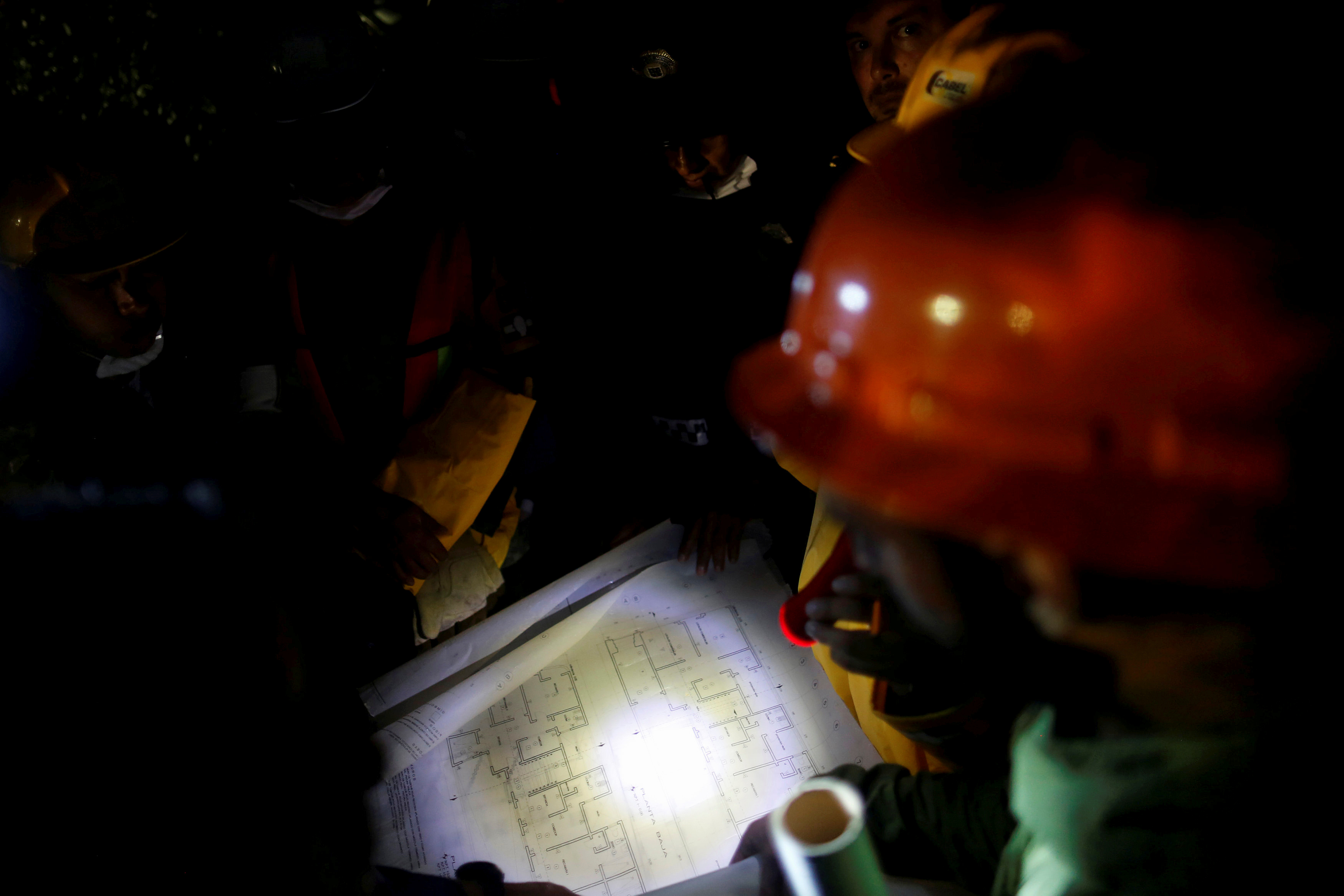 Rescue worker and Mexican soldiers study the drawing of a collapsed building as they search for survivors after an earthquake in Mexico City