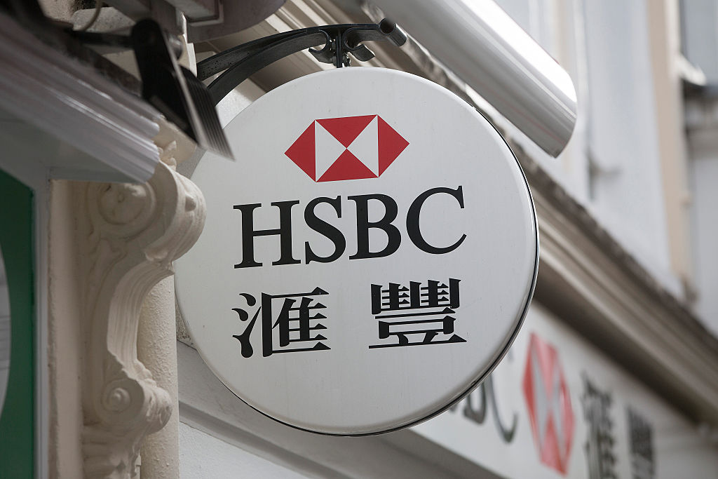 An HSBC logo with Chinese characters sits on display outside an HSBC Holdings Plc bank branch in London, U.K., on Tuesday, June 9, 2015. HSBC will eliminate as many as 50,000 jobs through 2017 by shrinking its global reach as Chief Executive Officer Stuart Gulliver seeks to cut annual costs by about $5 billion to restore profit growth. Photographer: Simon Dawson/Bloomberg