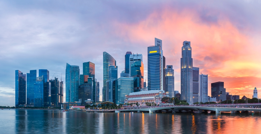 Singapore Skyline at Marina Bay at Twilight with glowing sunset illuminating the clouds