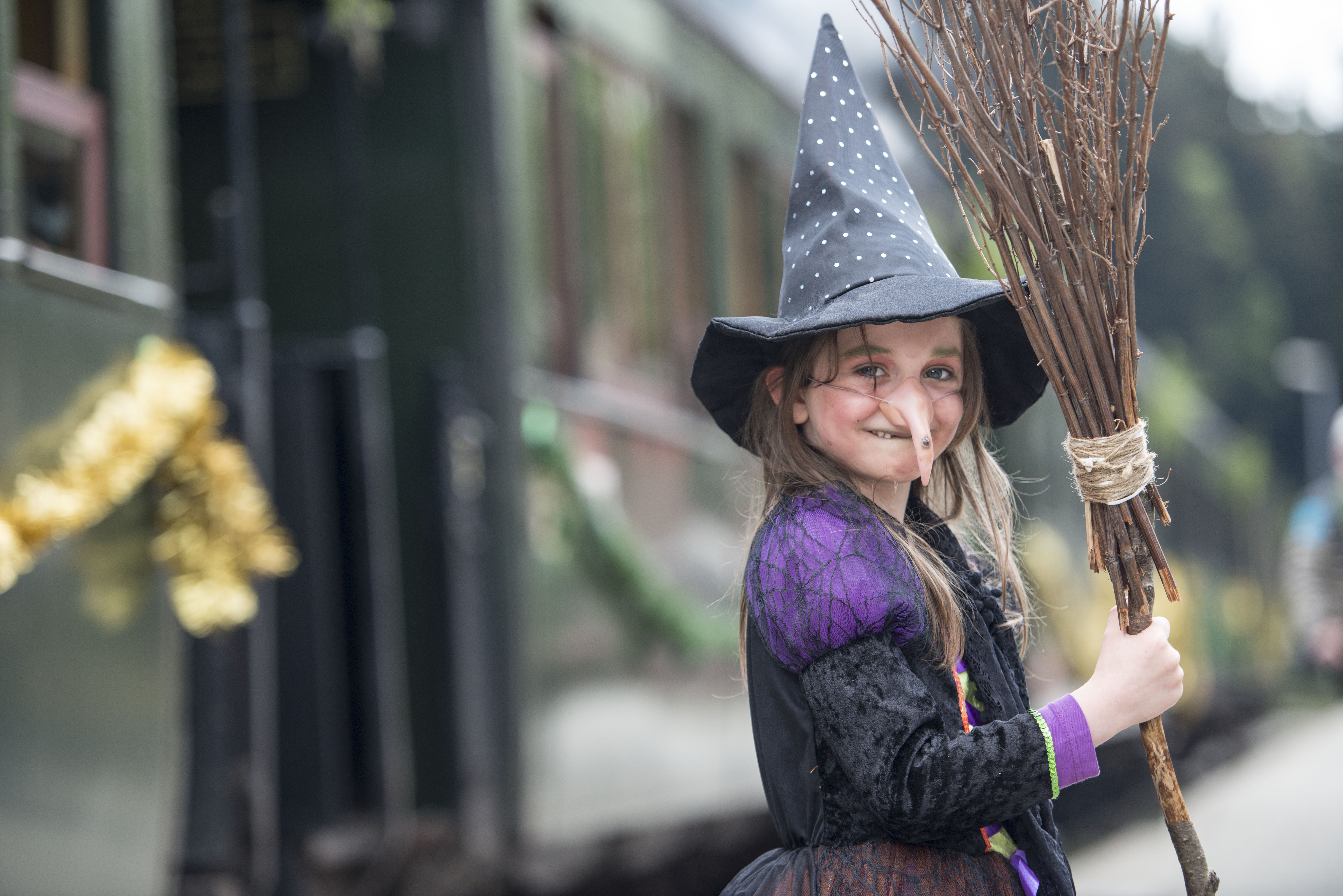 A little girl wearing a Halloween witch costume