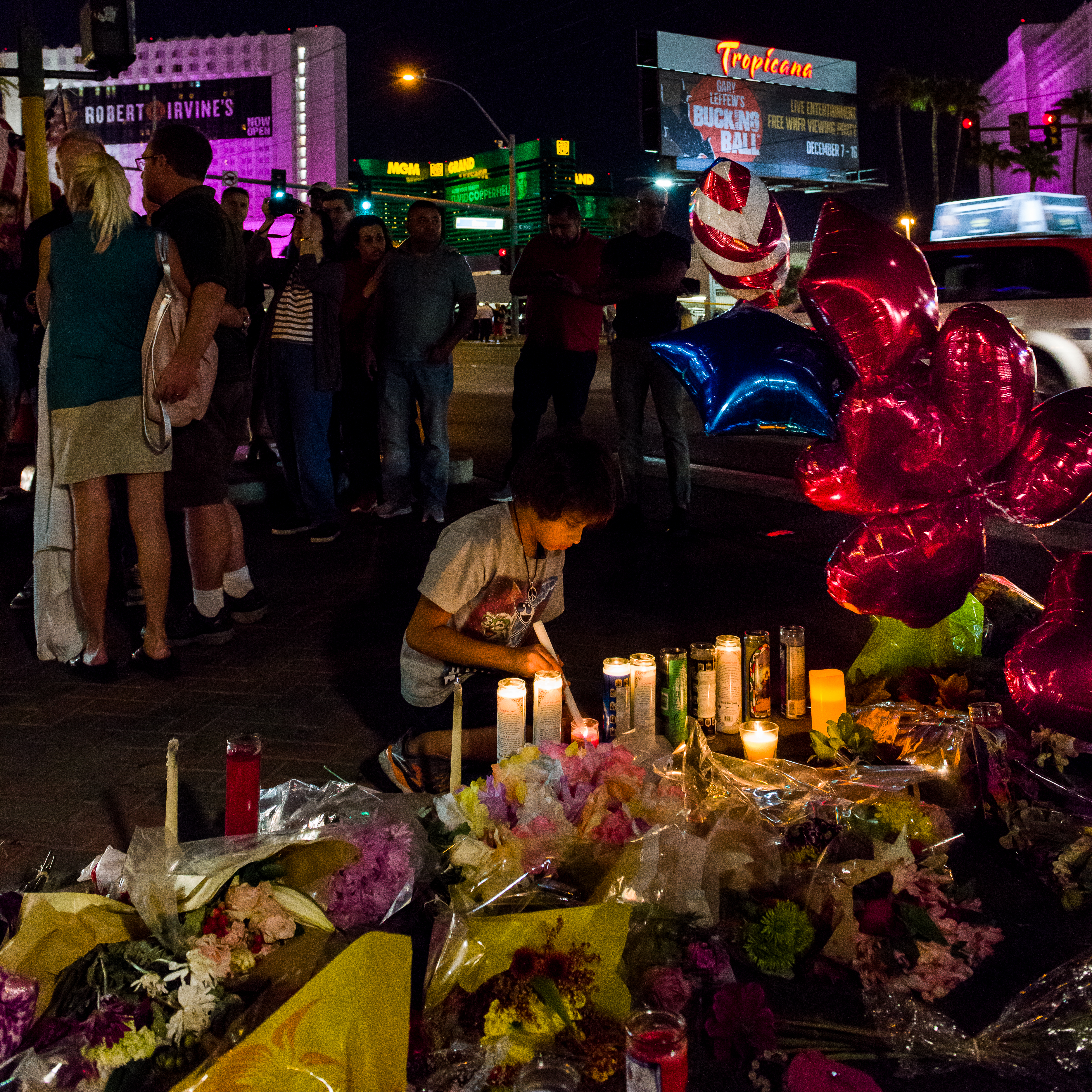 Child lights candles at a victims memorial vigil on Las Vegas Blvd. across from the Route 91 Festival location