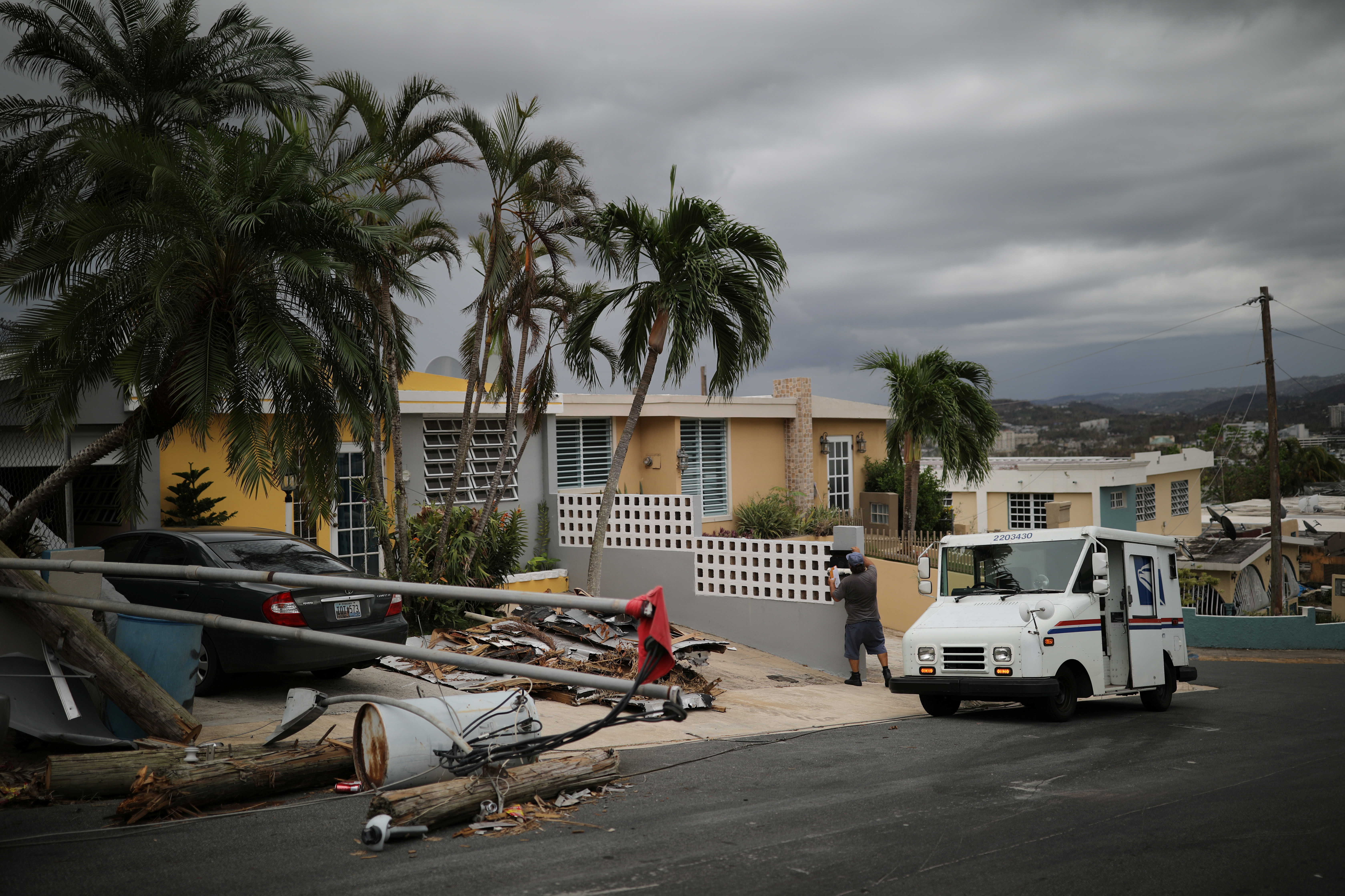 Alfredo Martinez, a mail man for the U.S. Postal Service delivers the mail at an area damaged by Hurricane Maria in San Juan, Puerto Rico