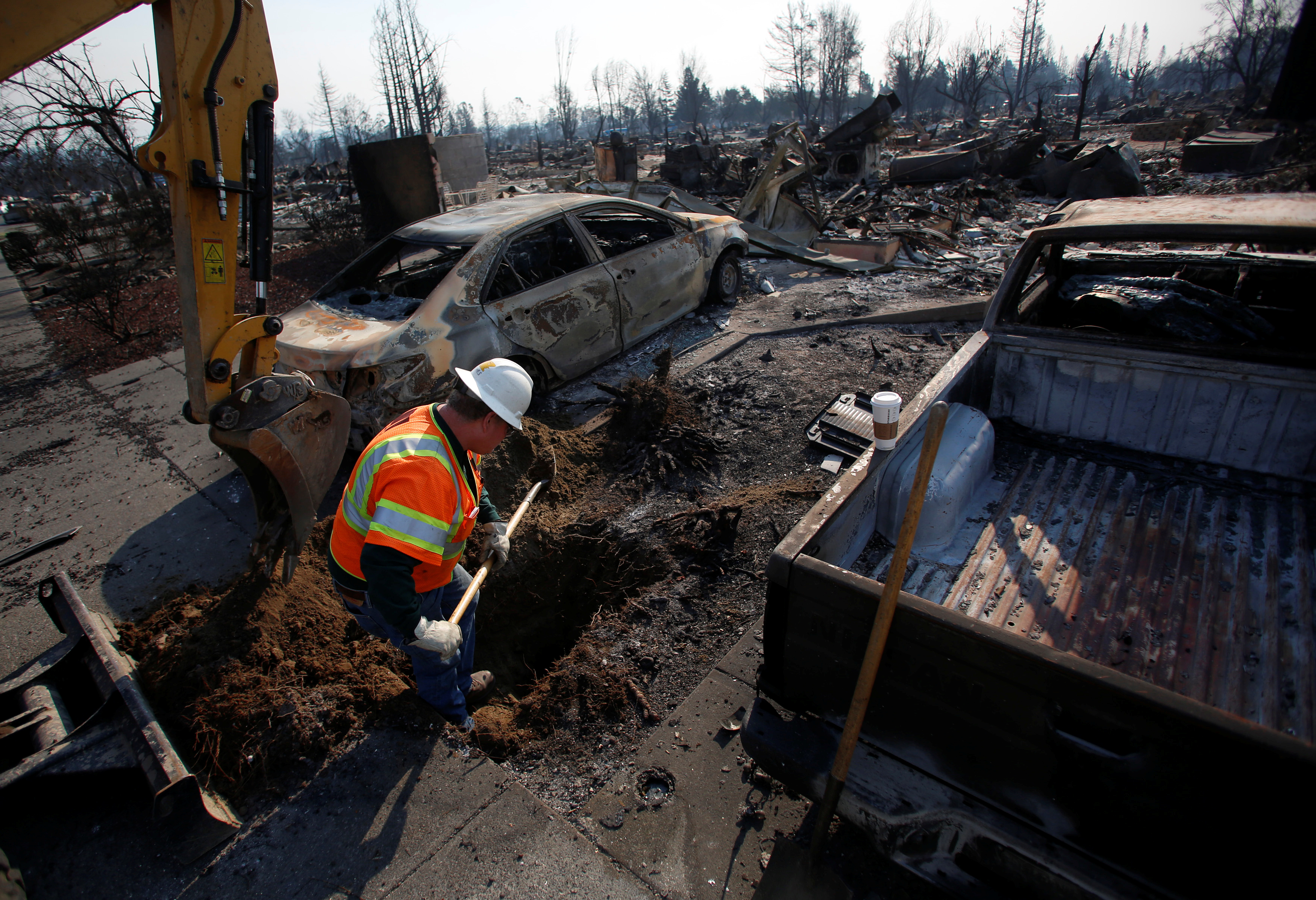 An employee of Pacific Gas & Electric (PG&E) digs to find an electrical transformer in a destroyed neighborhood after a wildfire tore through Santa Rosa, California