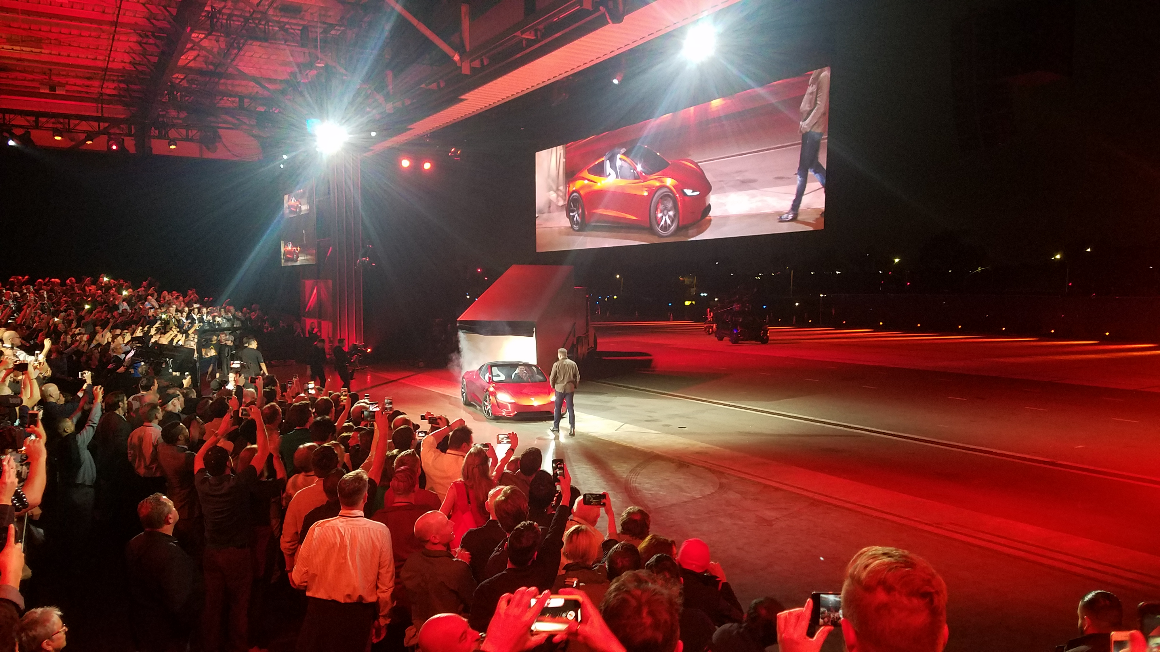 Tesla CEO Elon Musk stands as chief designer Franz von Holzhausen drives a prototype of the new Roadster from the back of the Tesla Semi.