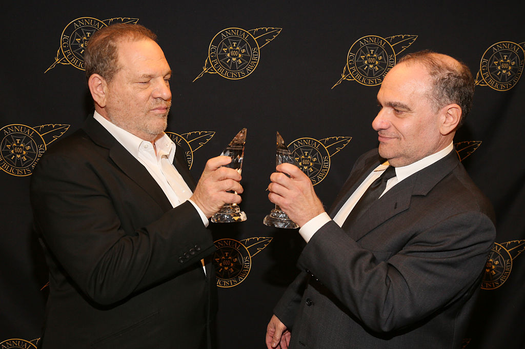 Harvey and Bob Weinstein toast each other.
