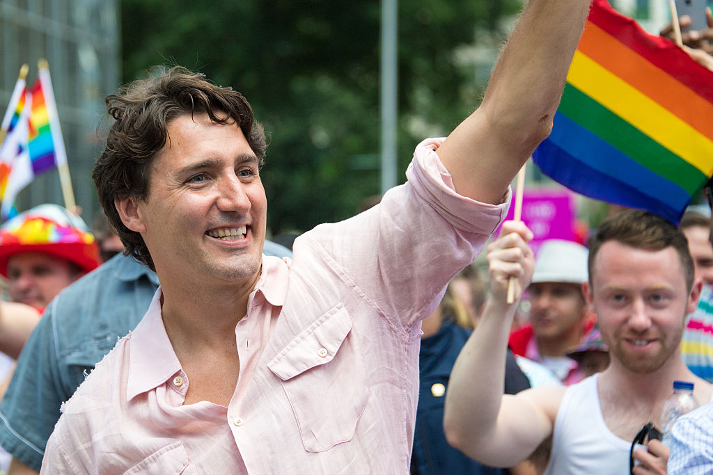 Justin Trudeau smiles and waves alongside LGBT flag at Pride parade