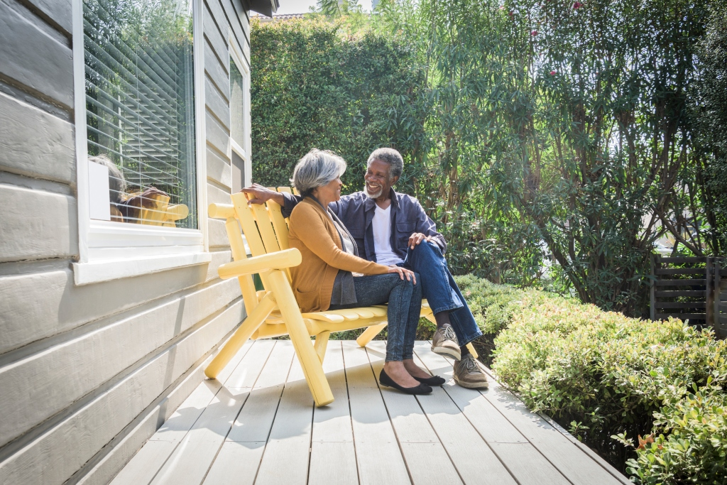 An older African American couple sitting on the porch of their house